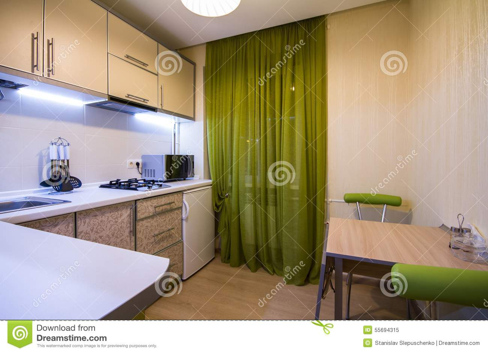 Moderne kleine keuken met groene gordijnen stock afbeelding
