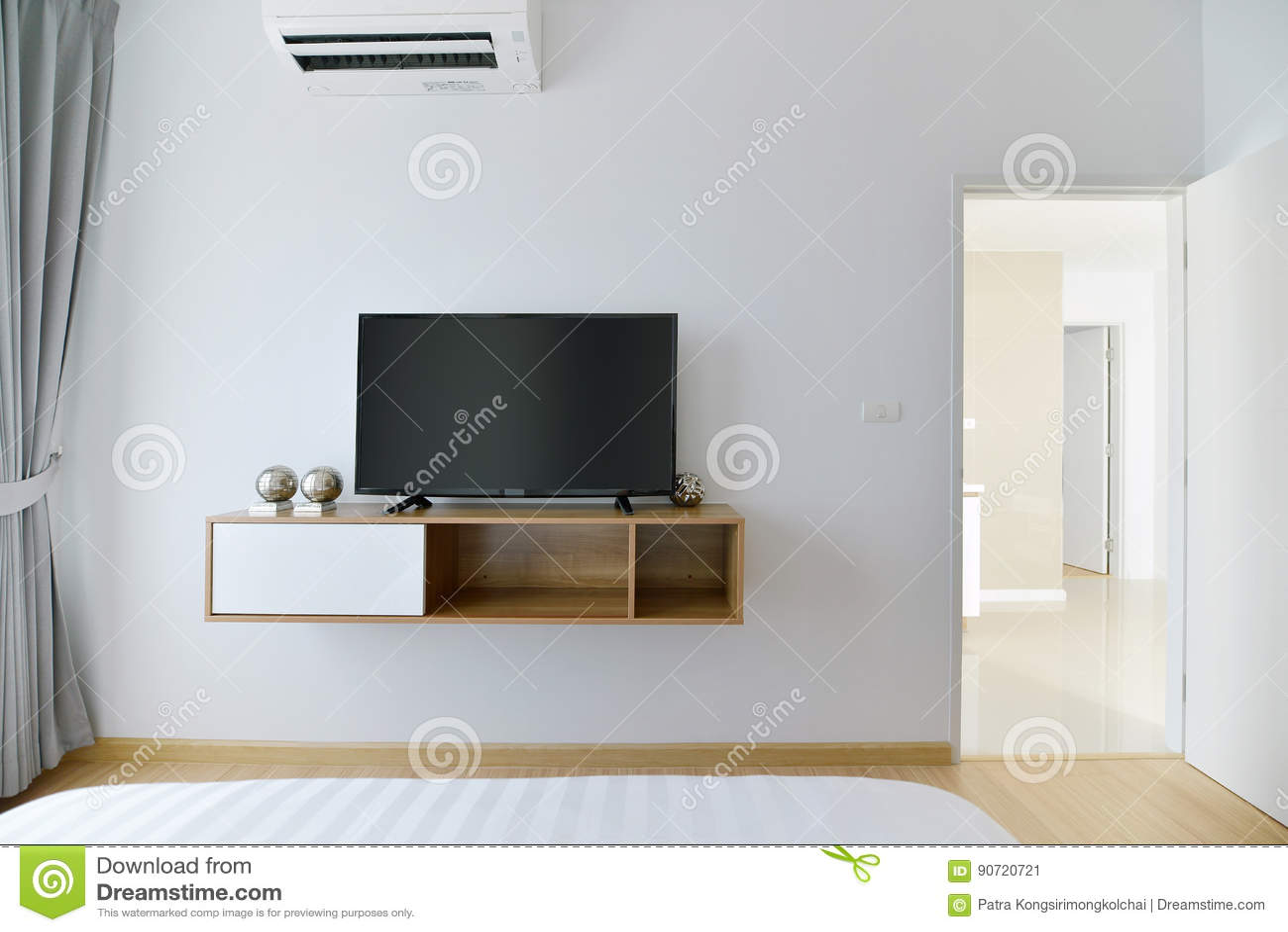 Moderne Lege Slaapkamer Met Geleide TV Op Witte Muur En Houten Plank Stock Afbeelding
