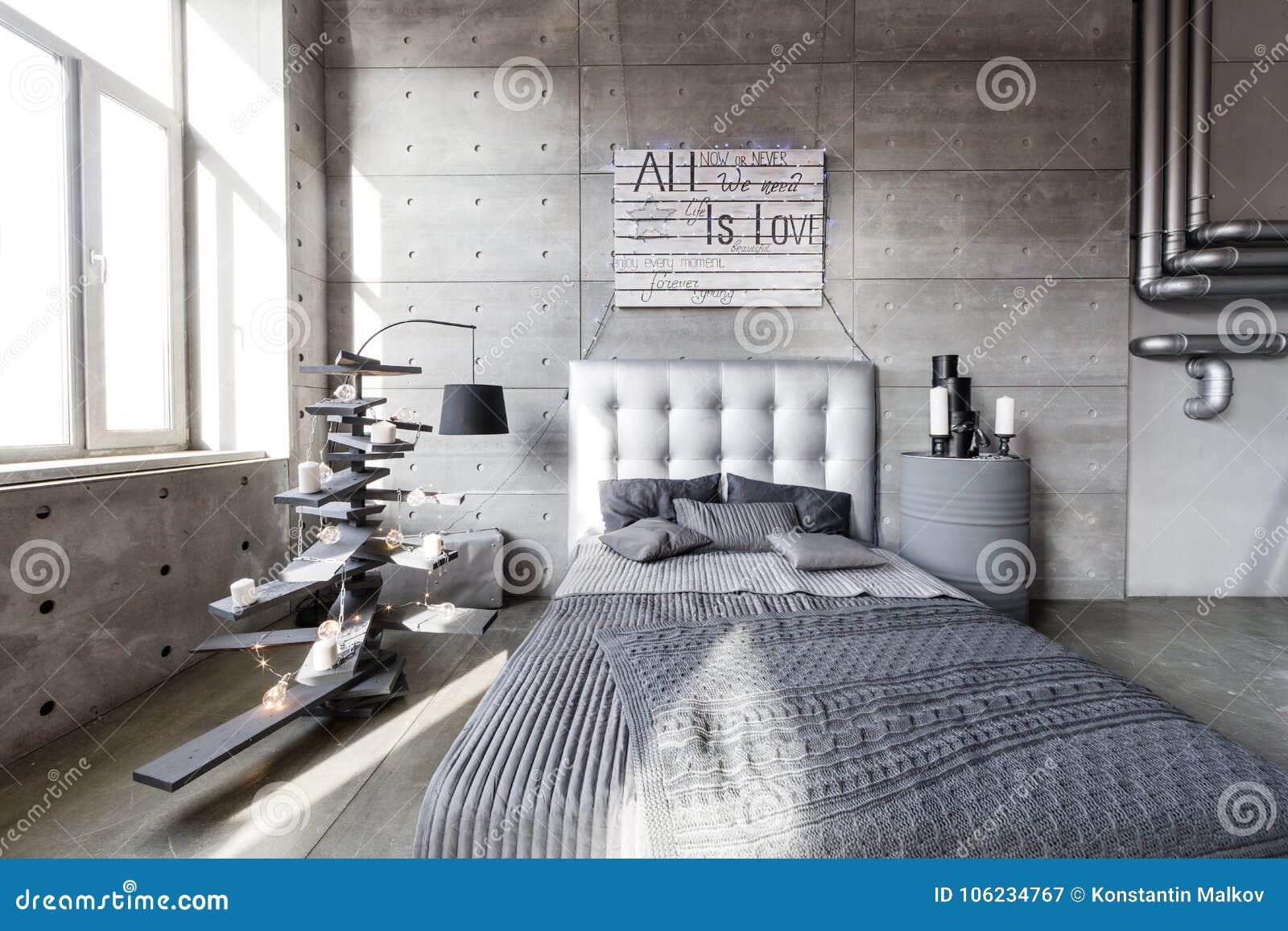 Moderne lege slaapkamer in zolderstijl met grijze kleuren en houten