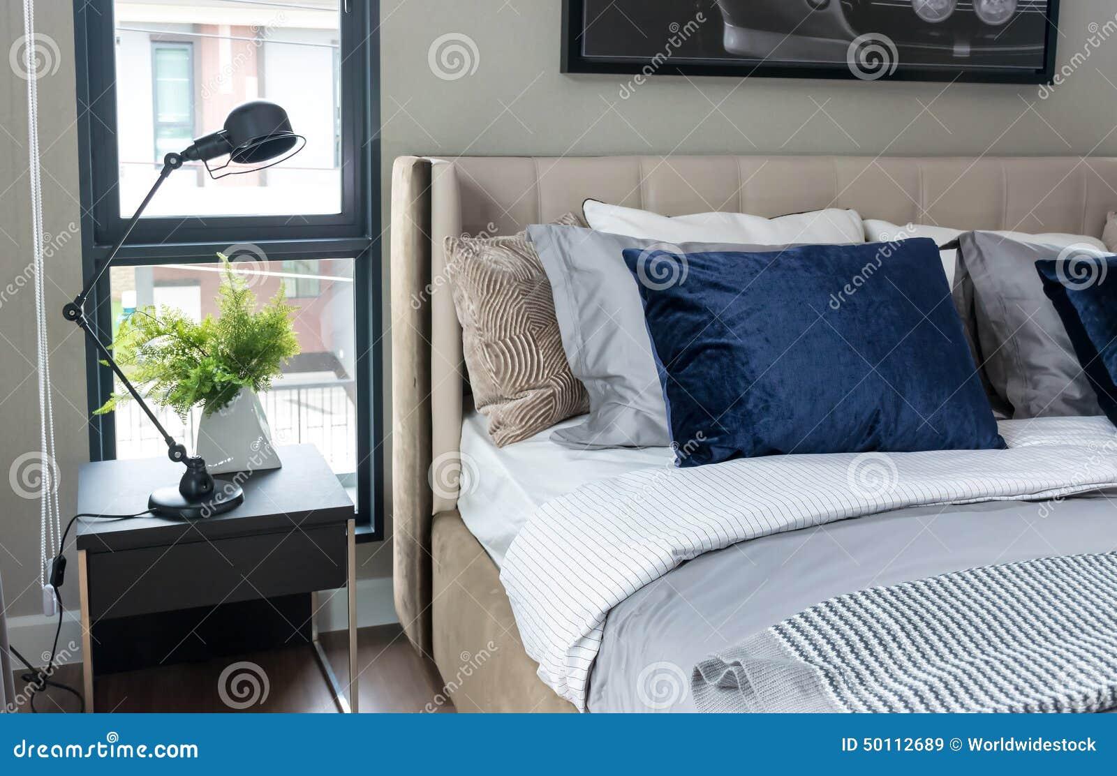 Blauwe Slaapkamer Lamp : Moderne slaapkamer met blauwe hoofdkussens en zwarte lamp op lijst