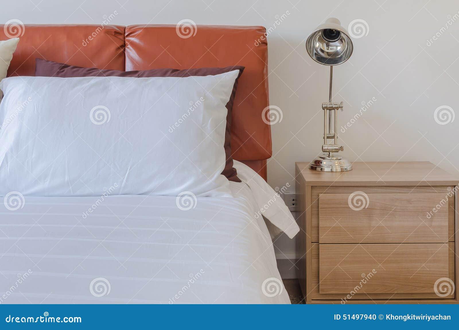 Moderne slaapkamer met leer bruin bed en moderne lamp op houten
