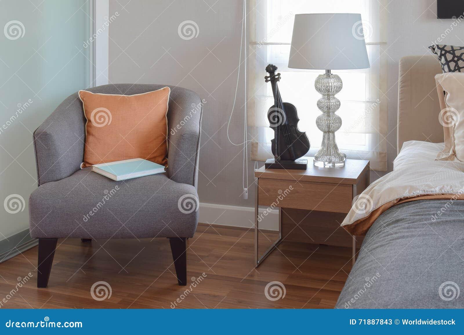Moderne slaapkamer met oranje hoofdkussen op grijs stoel en bed stock foto afbeelding 71887843 - Klassiek bed ...