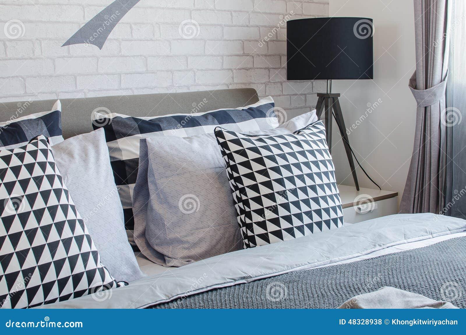 moderne slaapkamer met zwart witte hoofdkussens en zwarte lamp