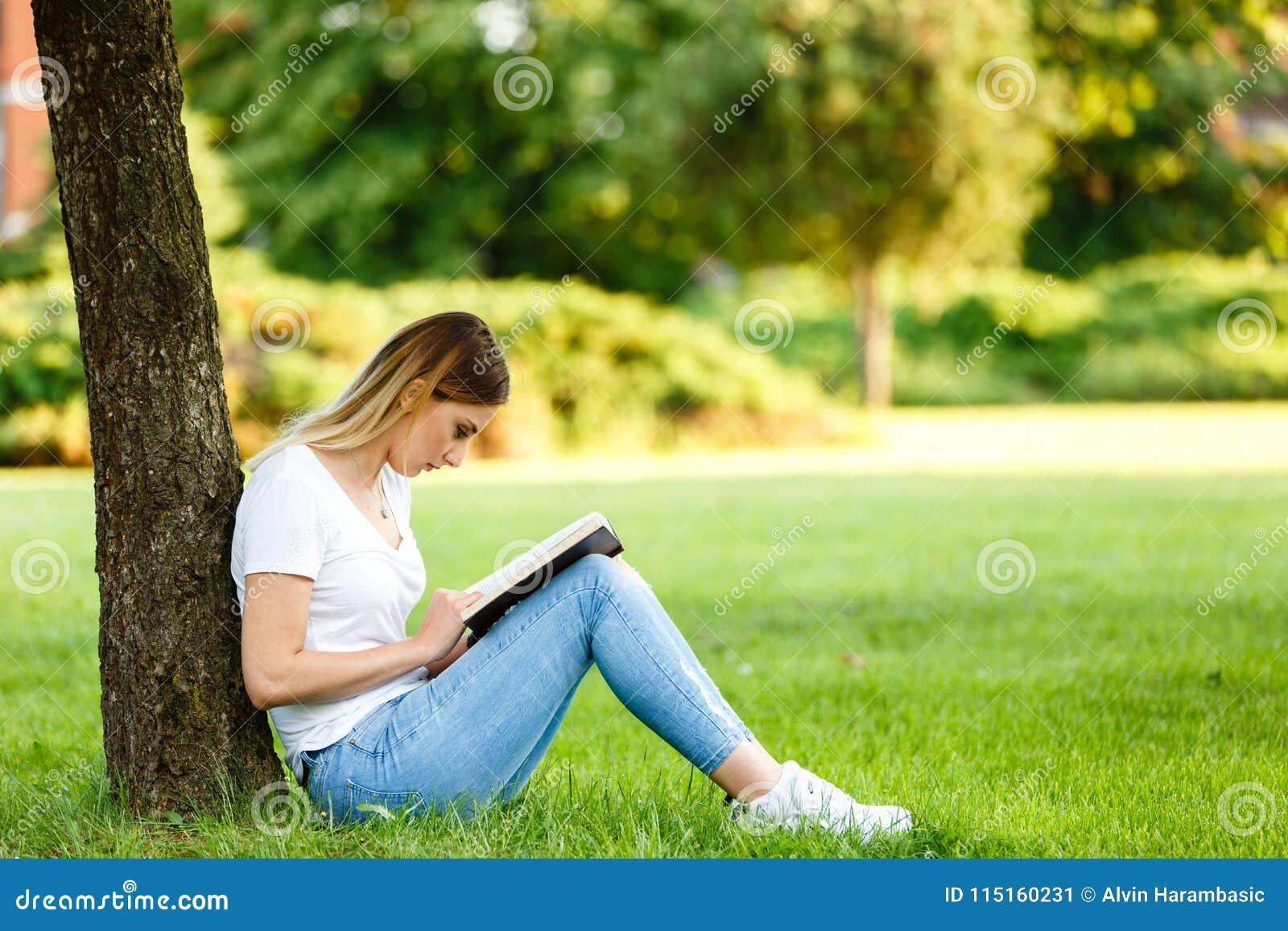 Moderne studentenzitting in park onder de boom en de lezing BO