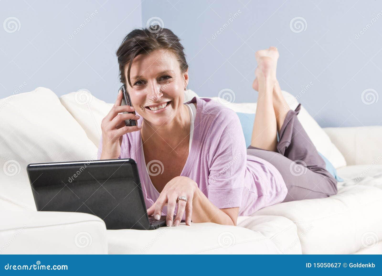 Moderne vrouw die op laag met telefoon, laptop wordt ontspannen