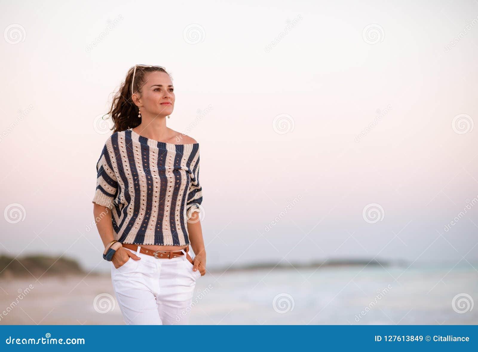 Moderne vrouw die op zeekust bij zonsondergang afstand onderzoeken