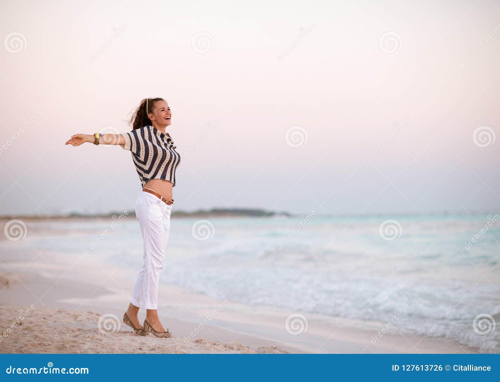 Moderne vrouw op strand bij zich zonsondergang het verheugen
