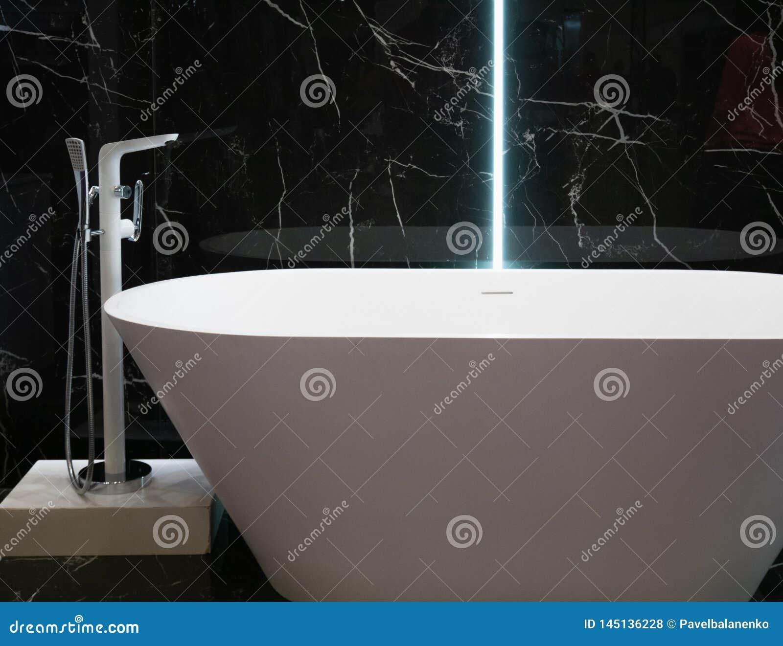 Moderne witte badkuip bij hotelflat met zwarte marmeren muur op achtergrond eigentijds binnenlands ontwerp bij badkamers