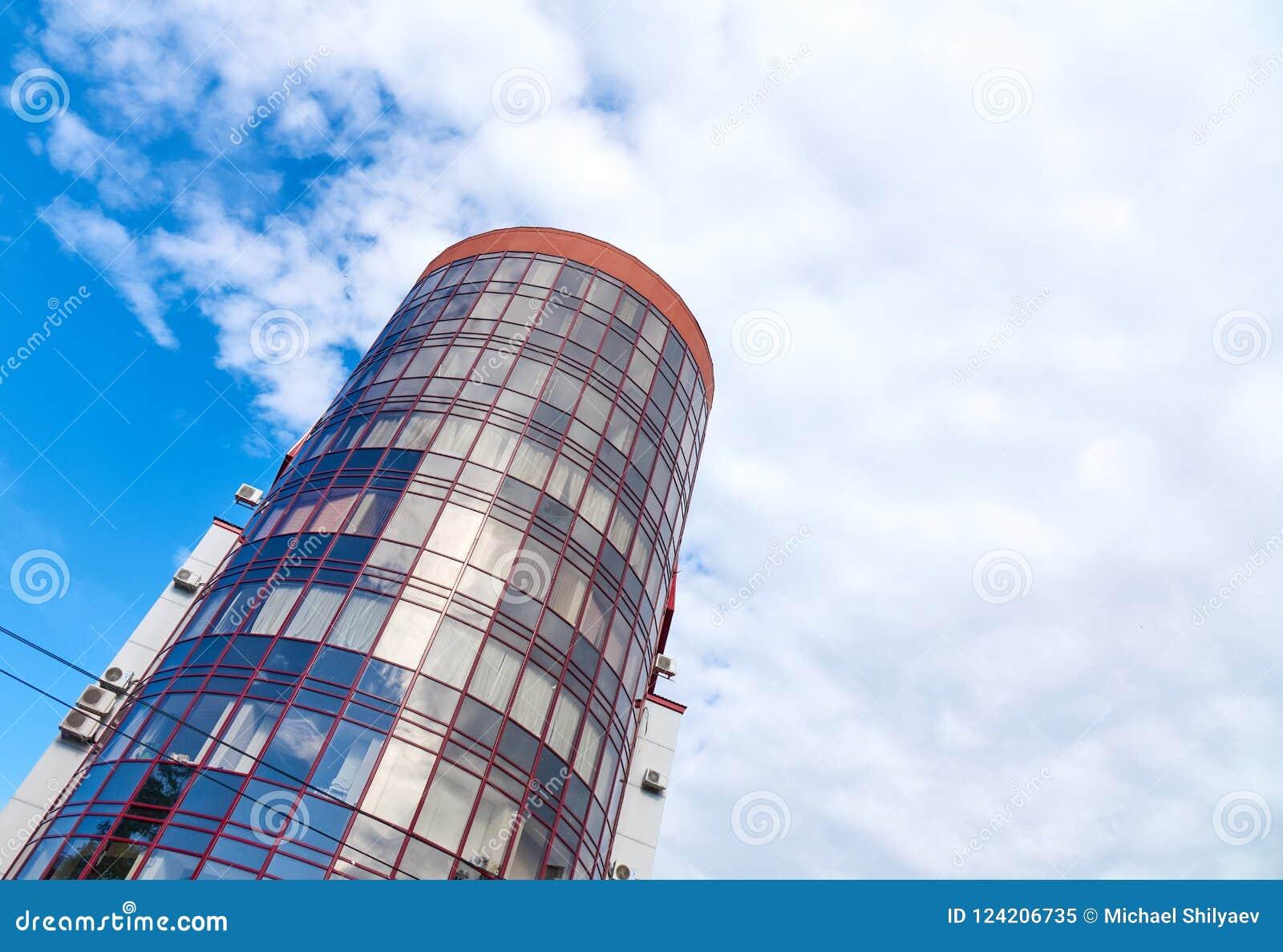 Moderne wolkenkrabber met een unieke ronde vorm, bewolkte hemelachtergrond, exemplaarruimte