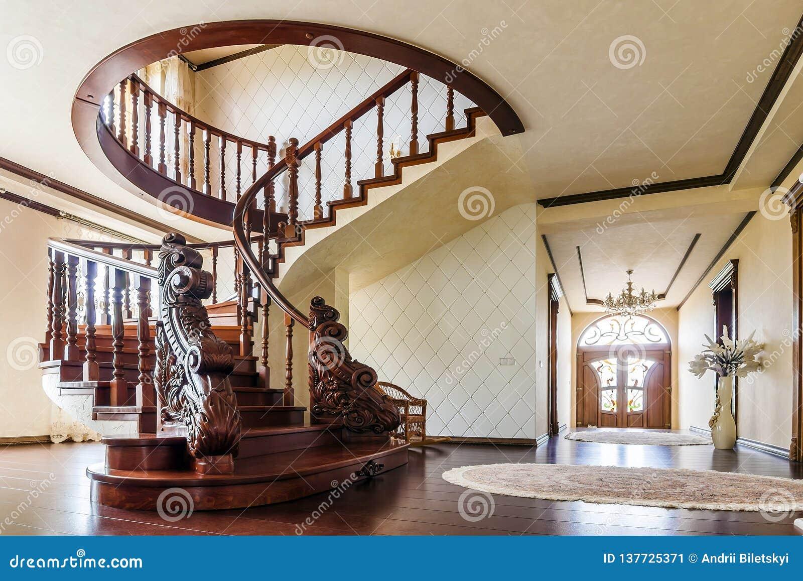 Moderner Architekturinnenraum mit klassischer eleganter Luxushalle mit gebogener glatter hölzerner Bügeltreppe im modernen Gescho