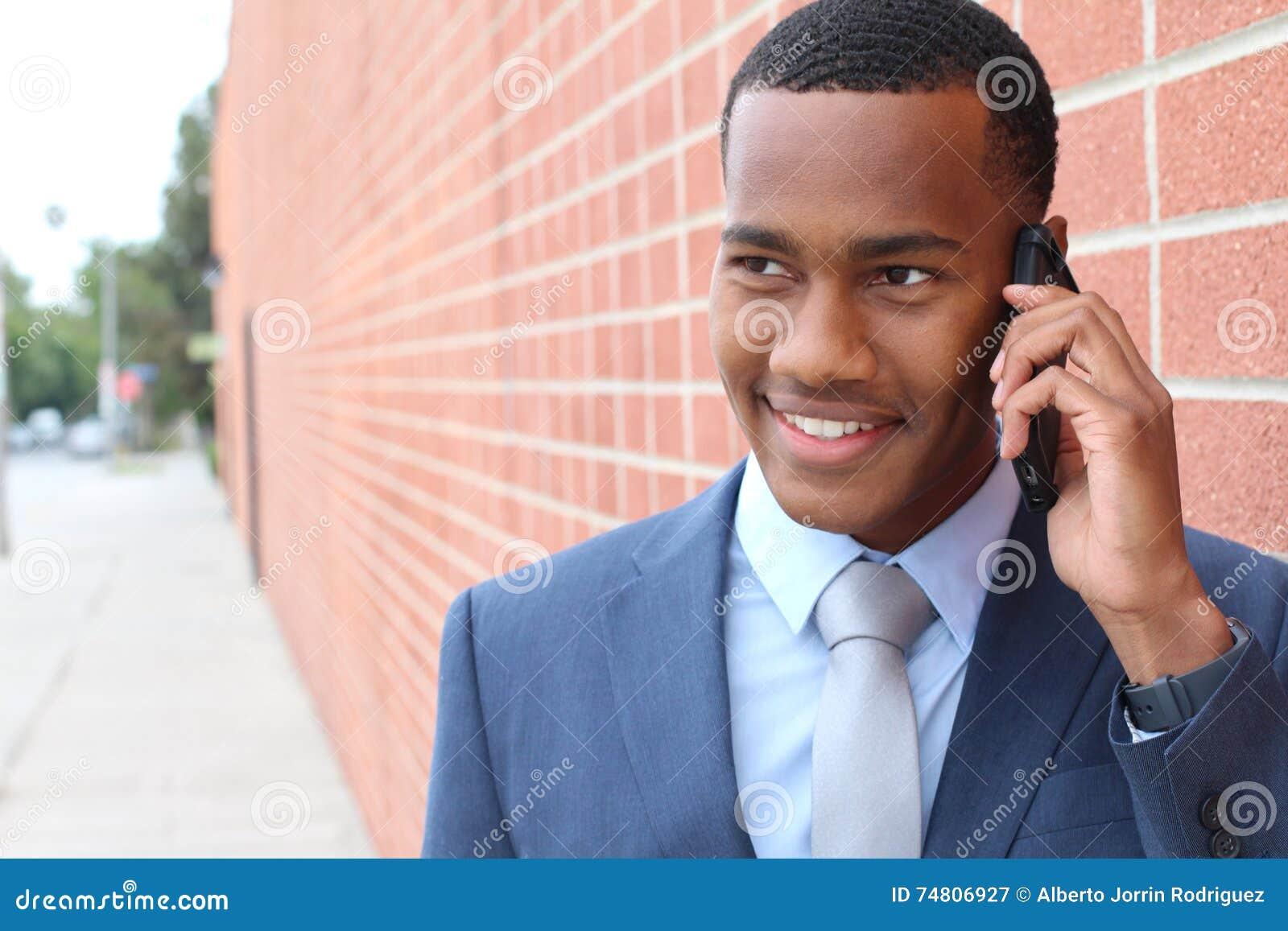 Moderner Geschäftsmann des hübschen Afroamerikaners, der in Stadt geht und um Handy ersucht