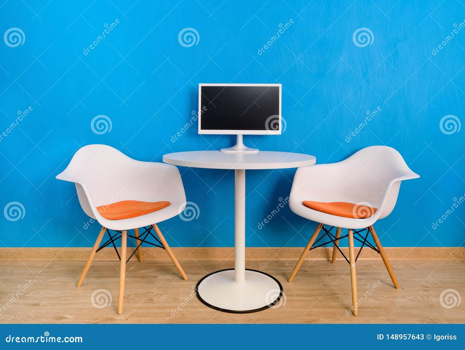 Moderner Innenbürotisch und zwei Stühle mit Computermonitor