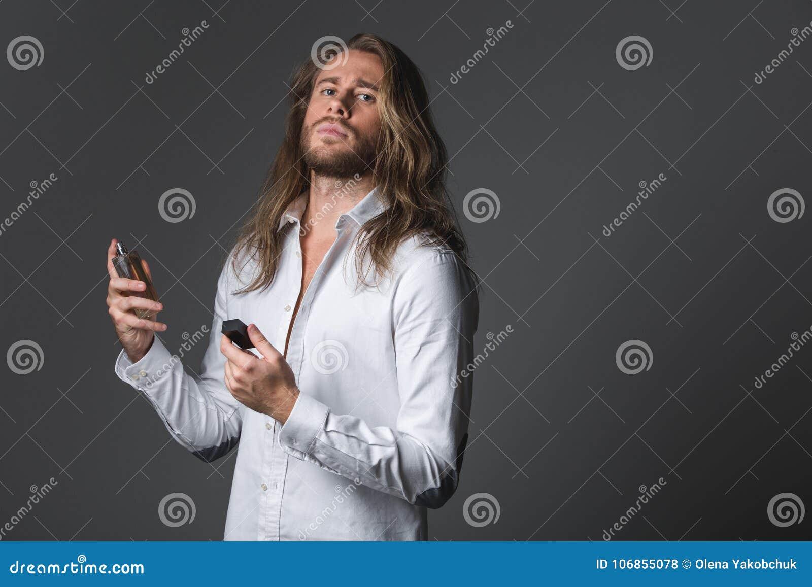 Moderner ruhiger Mann, der sich parfümiert