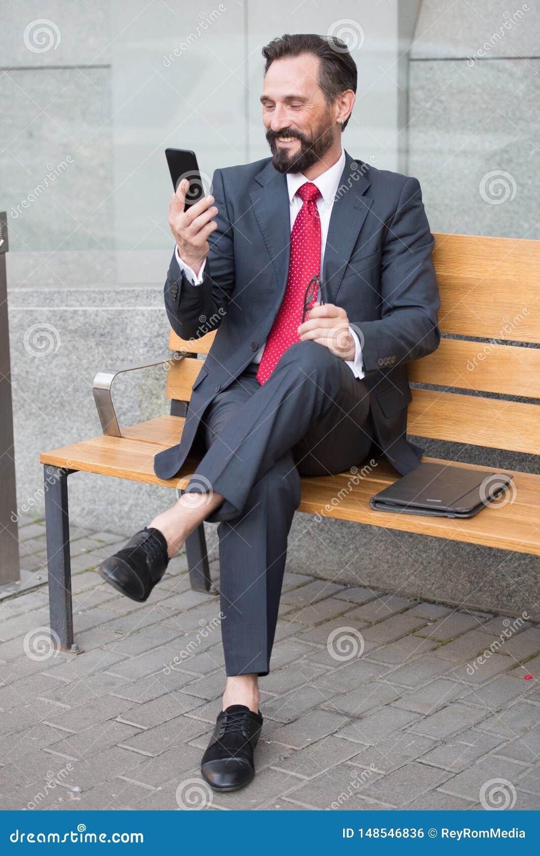 Moderner Unternehmer, der einen Smartphone beim Sitzen auf der Bank mit den gekreuzten Beinen verwendet