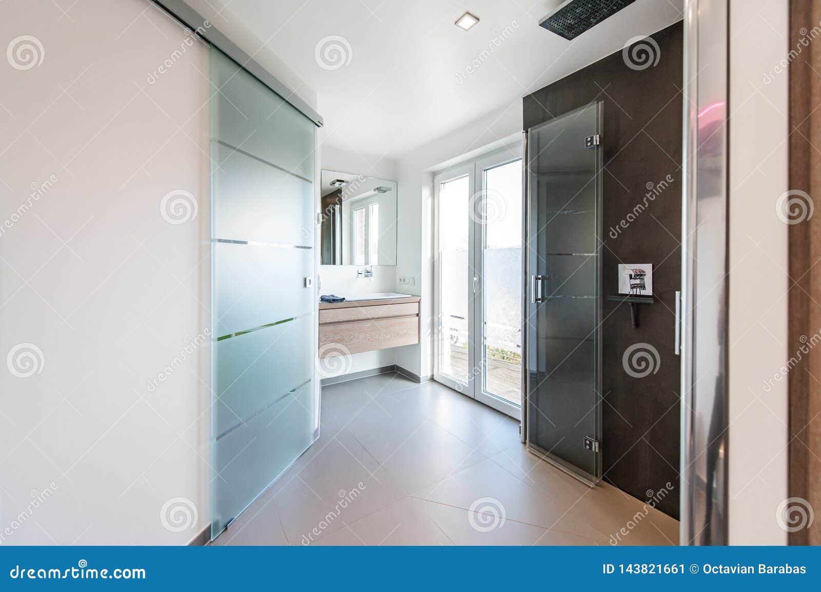 Modernes Badezimmer mit Glastüren und Duschkabine