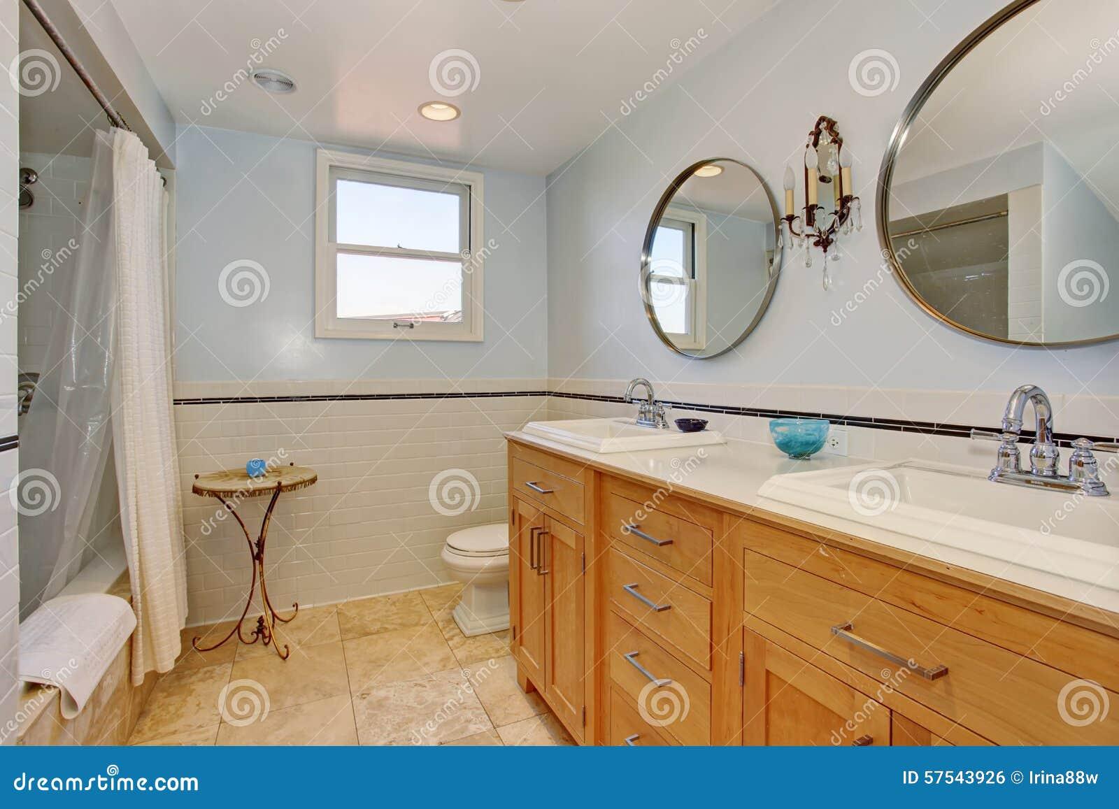Modernes badezimmer mit zwei ovalen spiegeln und weißer duschvorhang