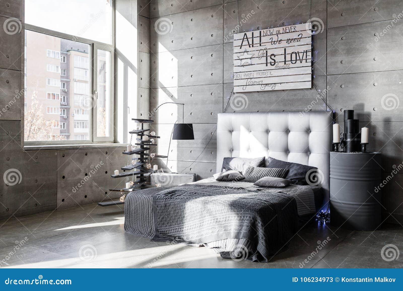 Modernes leeres Schlafzimmer in der Dachbodenart mit grauen Farben und im hölzernen handgemachten Weihnachtsbaum mit Geschenken