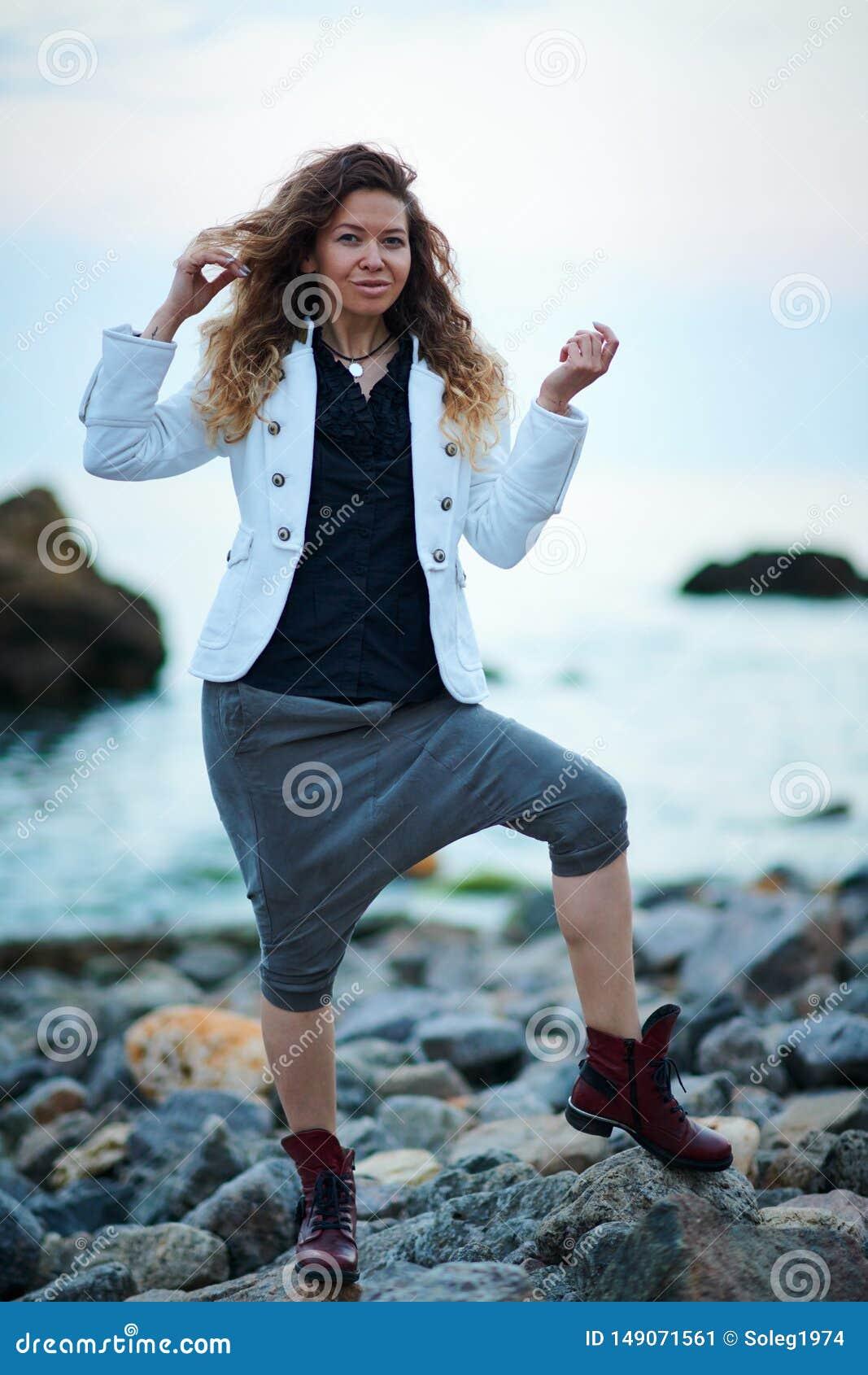 Modernes M?dchen gekleidet in der wei?en Jacke und breiten in der Hose, die nahe Meer am Abend aufwirft