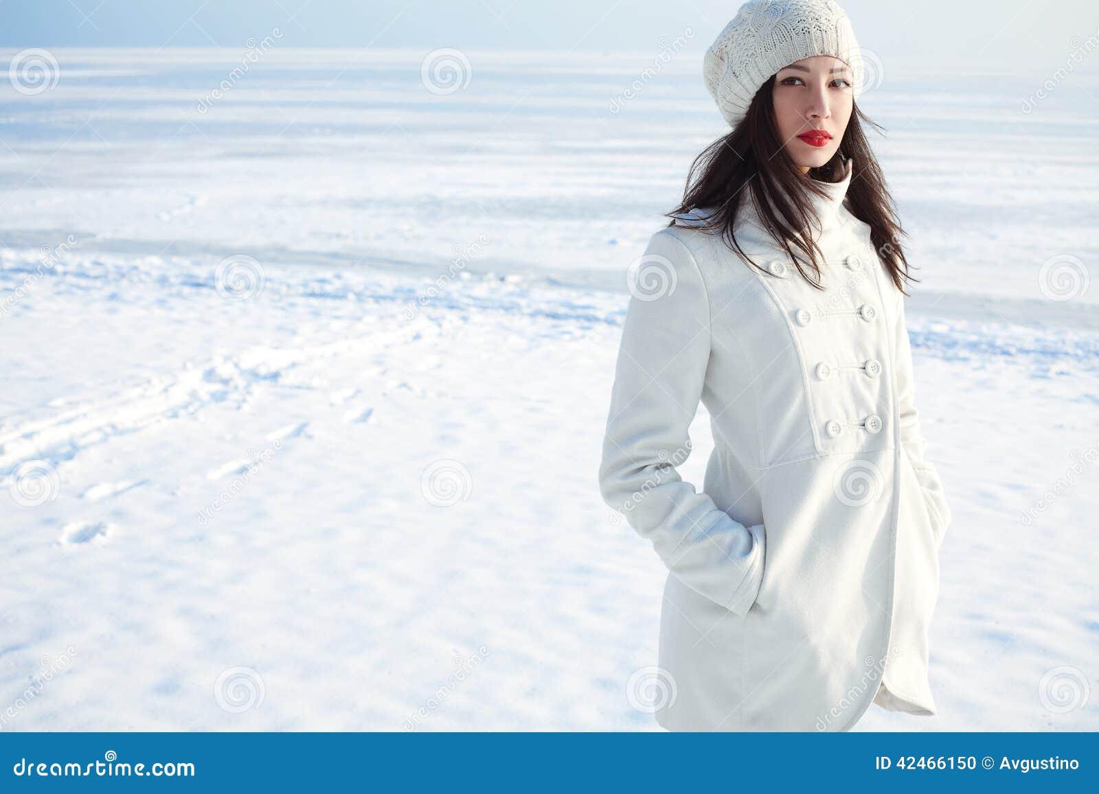Modernes Modell im weißen Mantel nahe Wintermeer