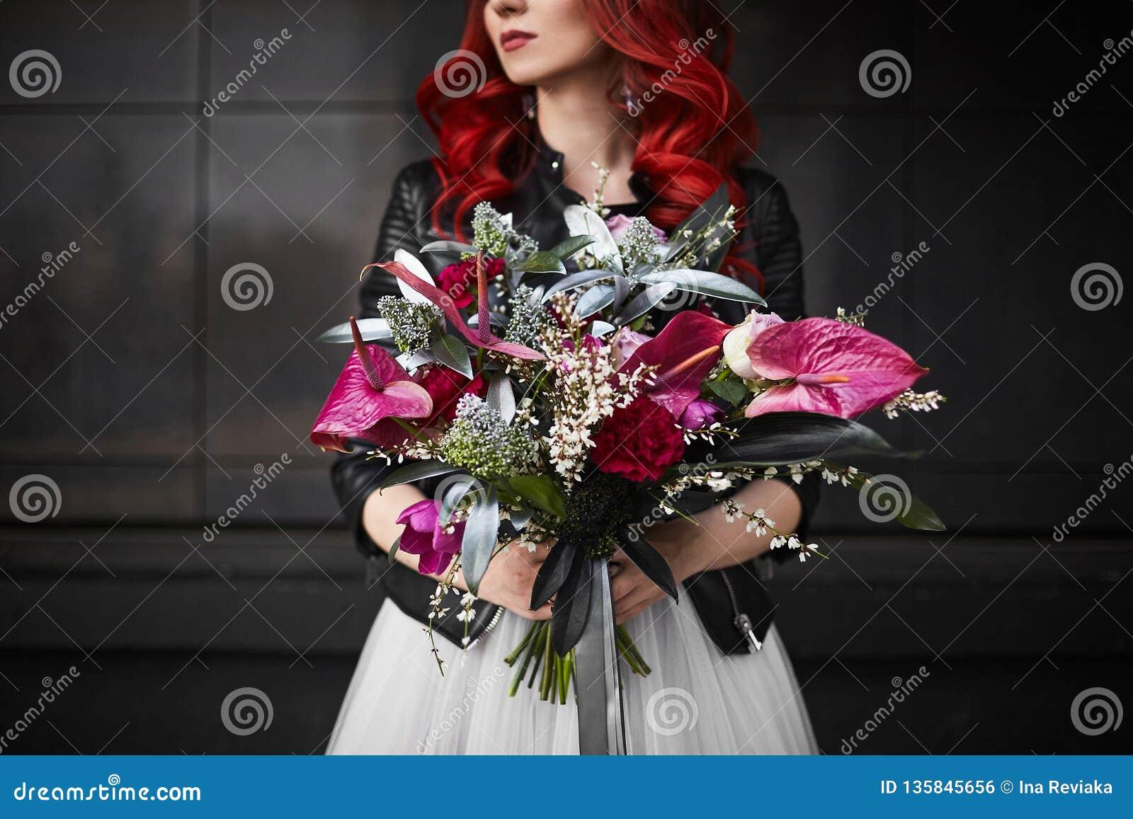 Modernes und schönes vorbildliches Mädchen mit dem roten Haar und hellem Make-up, in einem weißen Heiratskleid und in einer Leder