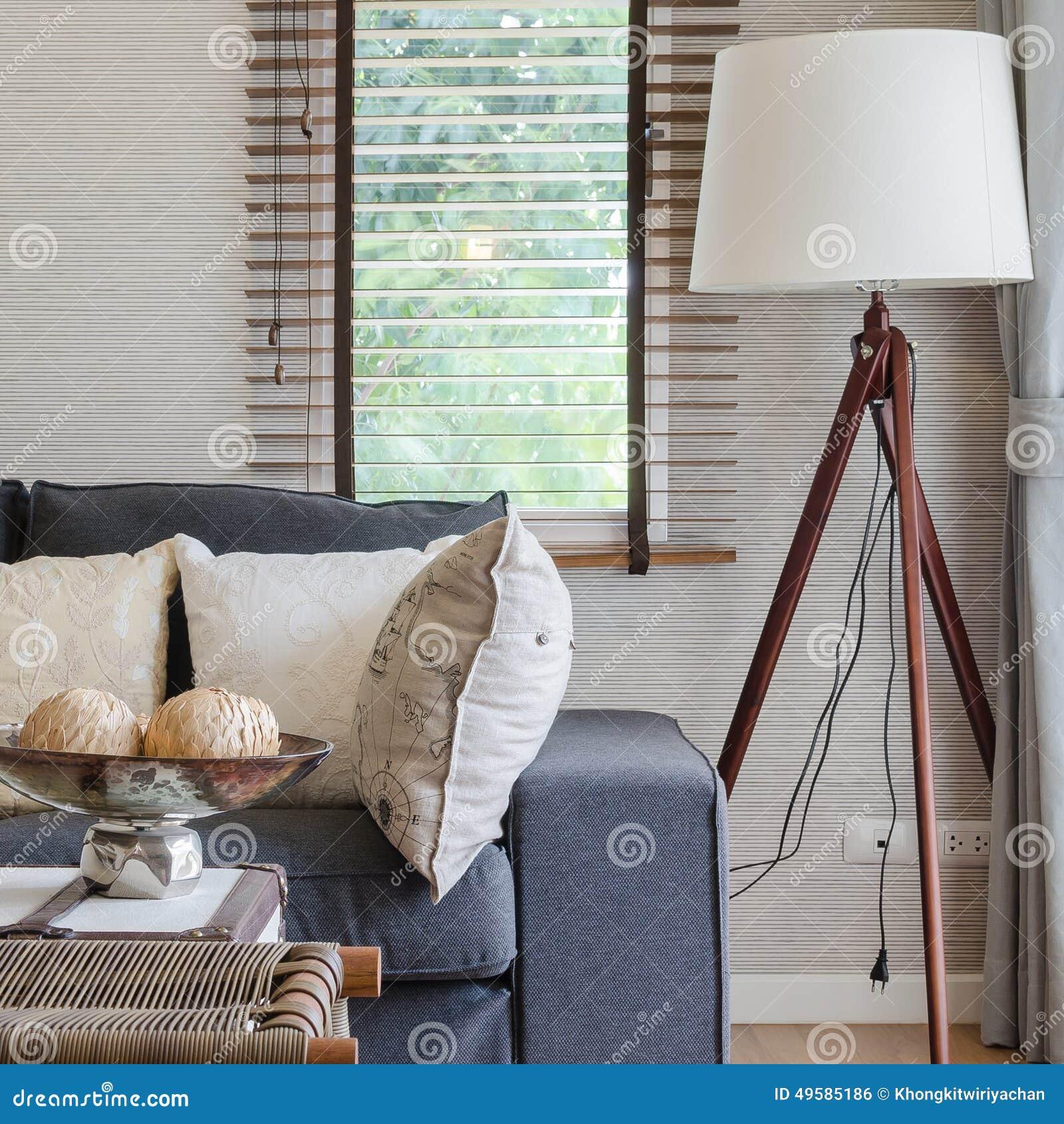 Modernes wohnzimmer mit schwarzem sofa und hölzerner lampe