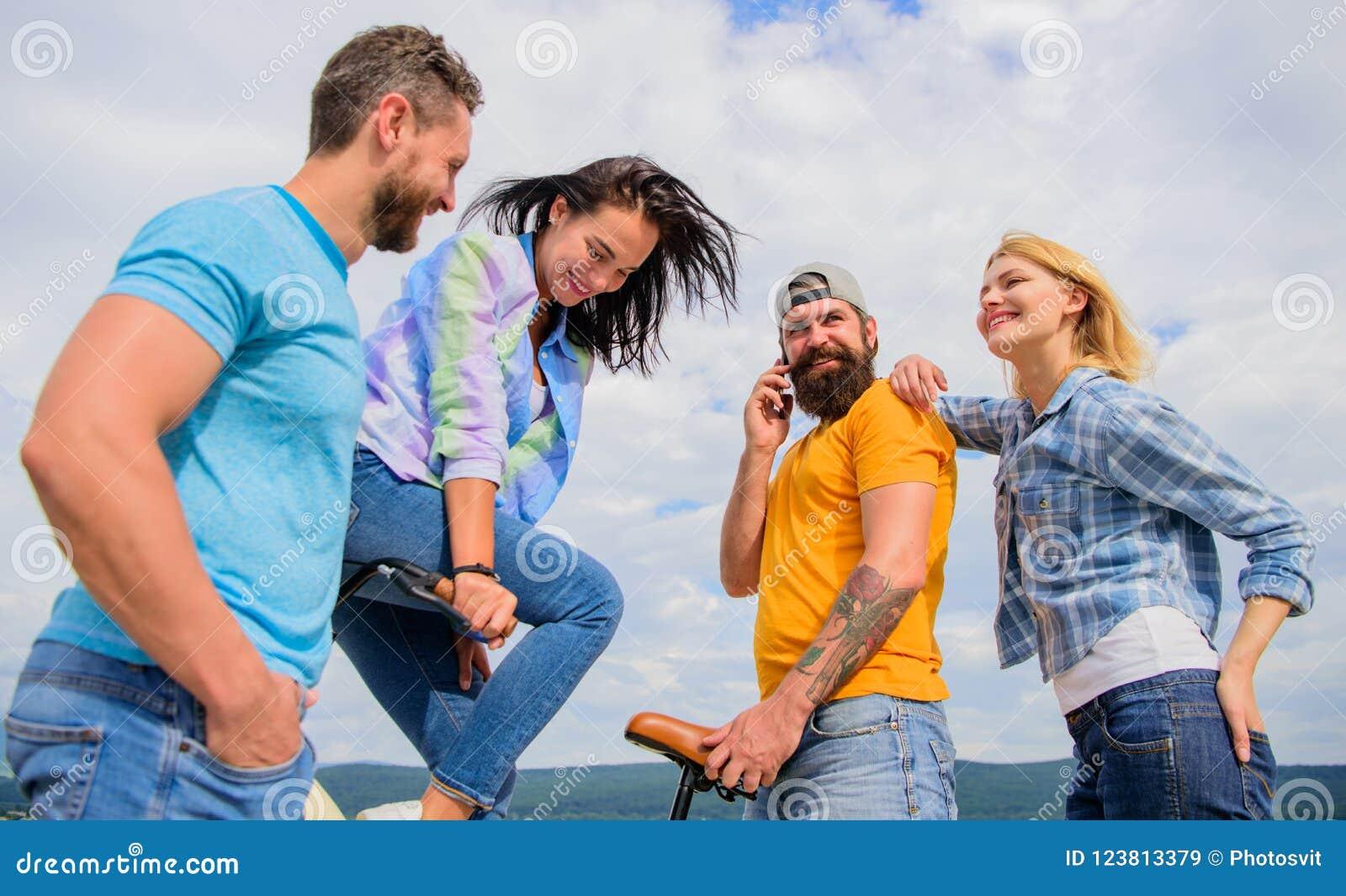 Modernidade do ciclismo e cultura nacional Conceito da data dobro Os amigos do grupo penduram para fora com bicicleta Jovens à mo