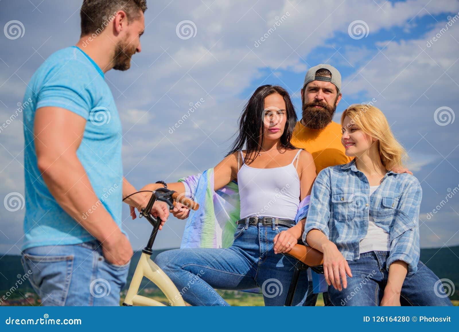 Modernidade do ciclismo e cultura nacional Os amigos do grupo penduram para fora com bicicleta Os jovens à moda da empresa gastam