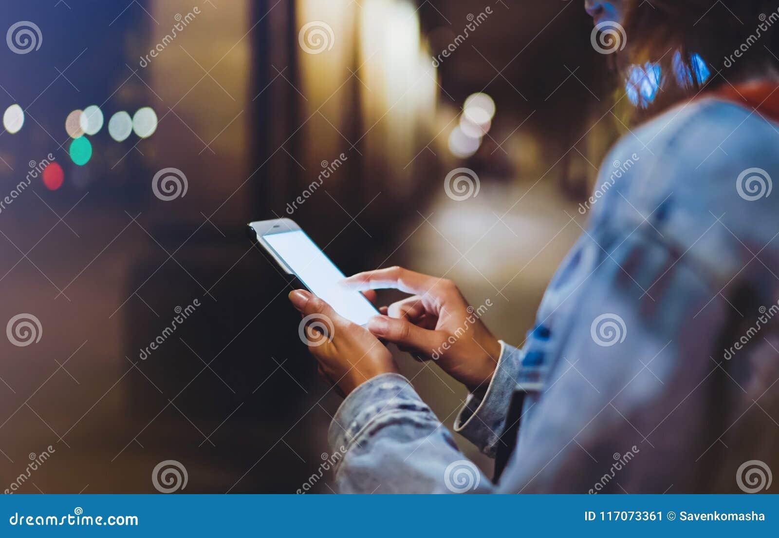 Moderno do Blogger que usa-se no telefone celular do dispositivo das mãos, mulher com trouxa que aponta o dedo no smartphone da t