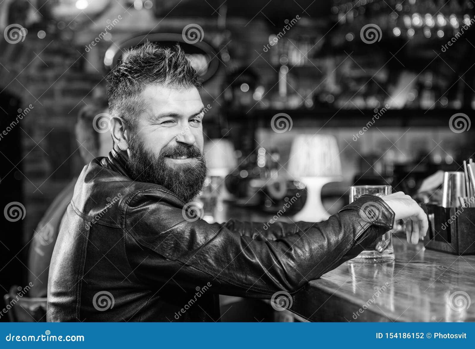 Moderno que relaxa na barra com cerveja O homem farpado do moderno brutal senta-se na cerveja da bebida do contador da barra Bebi