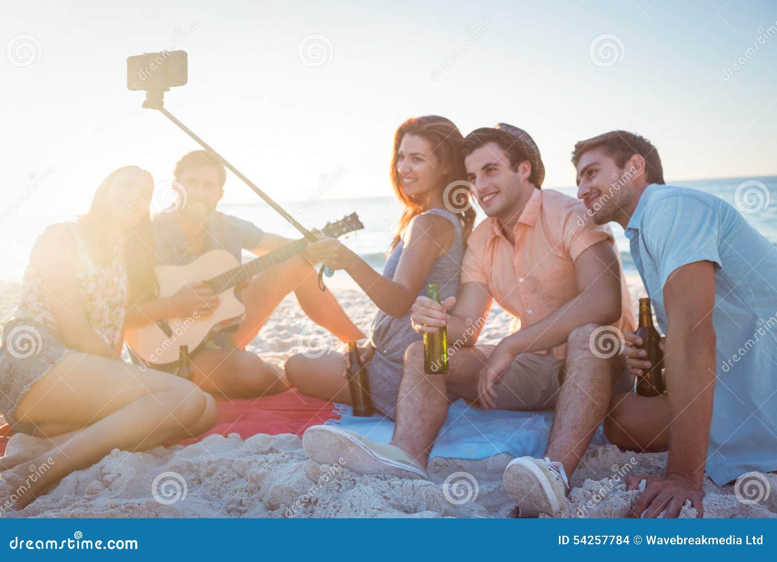 Modernos felizes que tomam imagens com vara do selfie