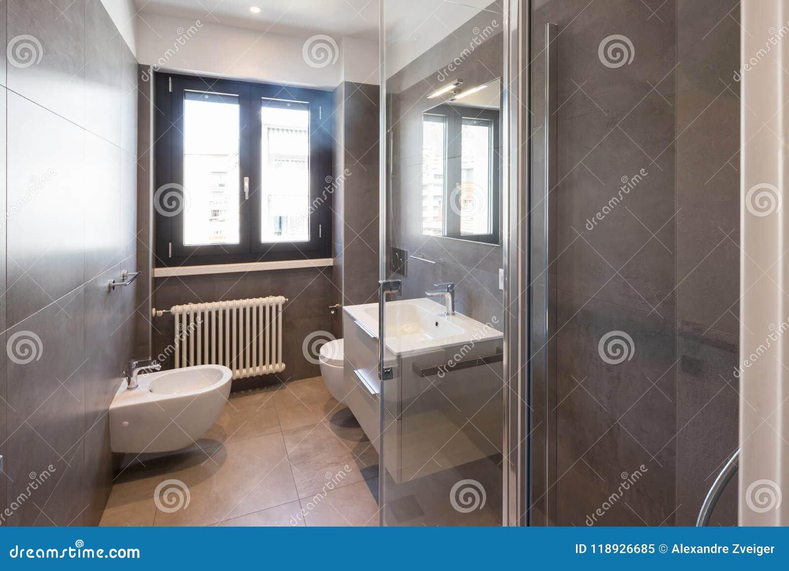 Modernt badrum med stora tegelplattor