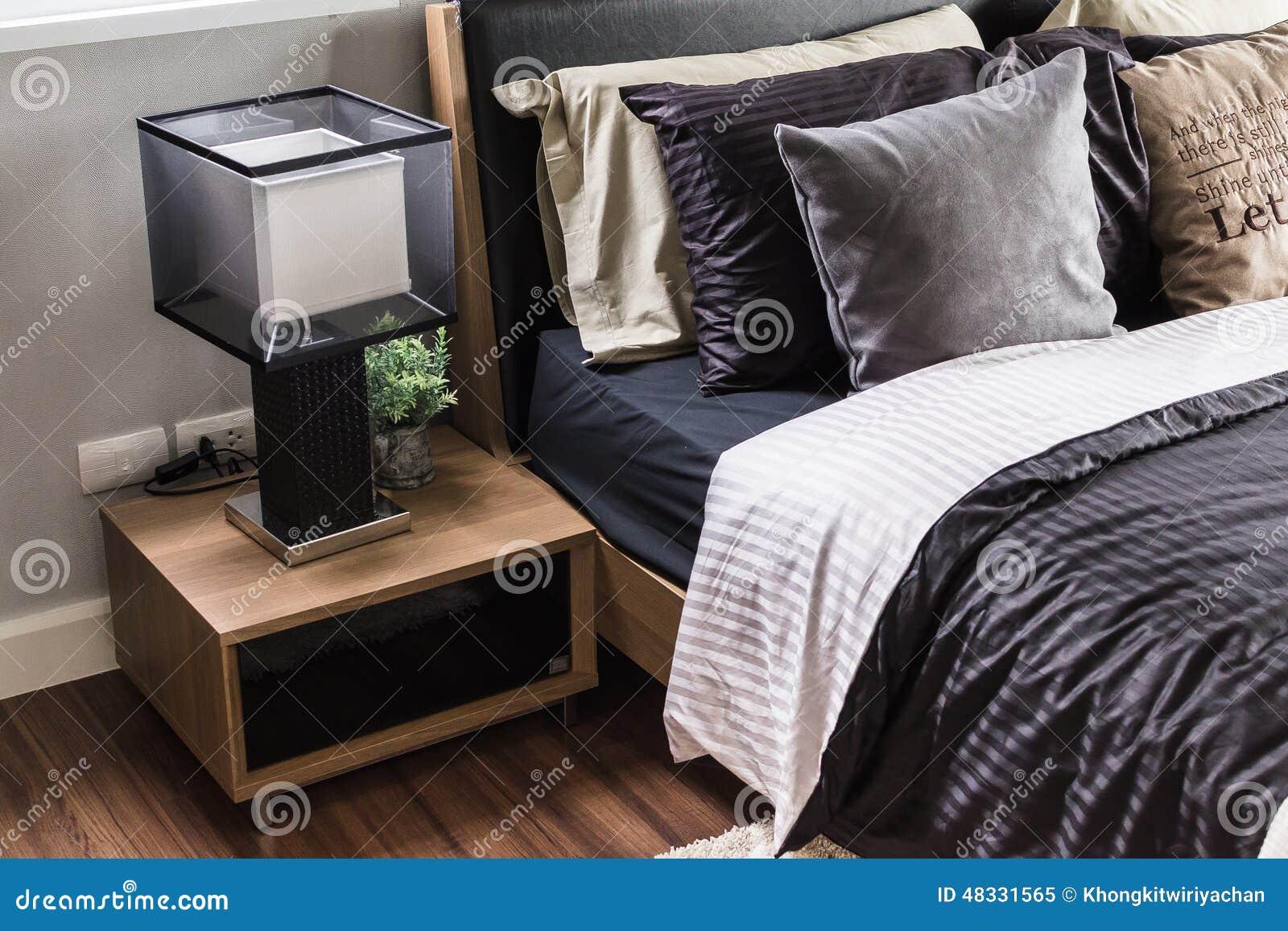 Modernt grått sovrum med den tränightstand och lampan arkivfoto ...