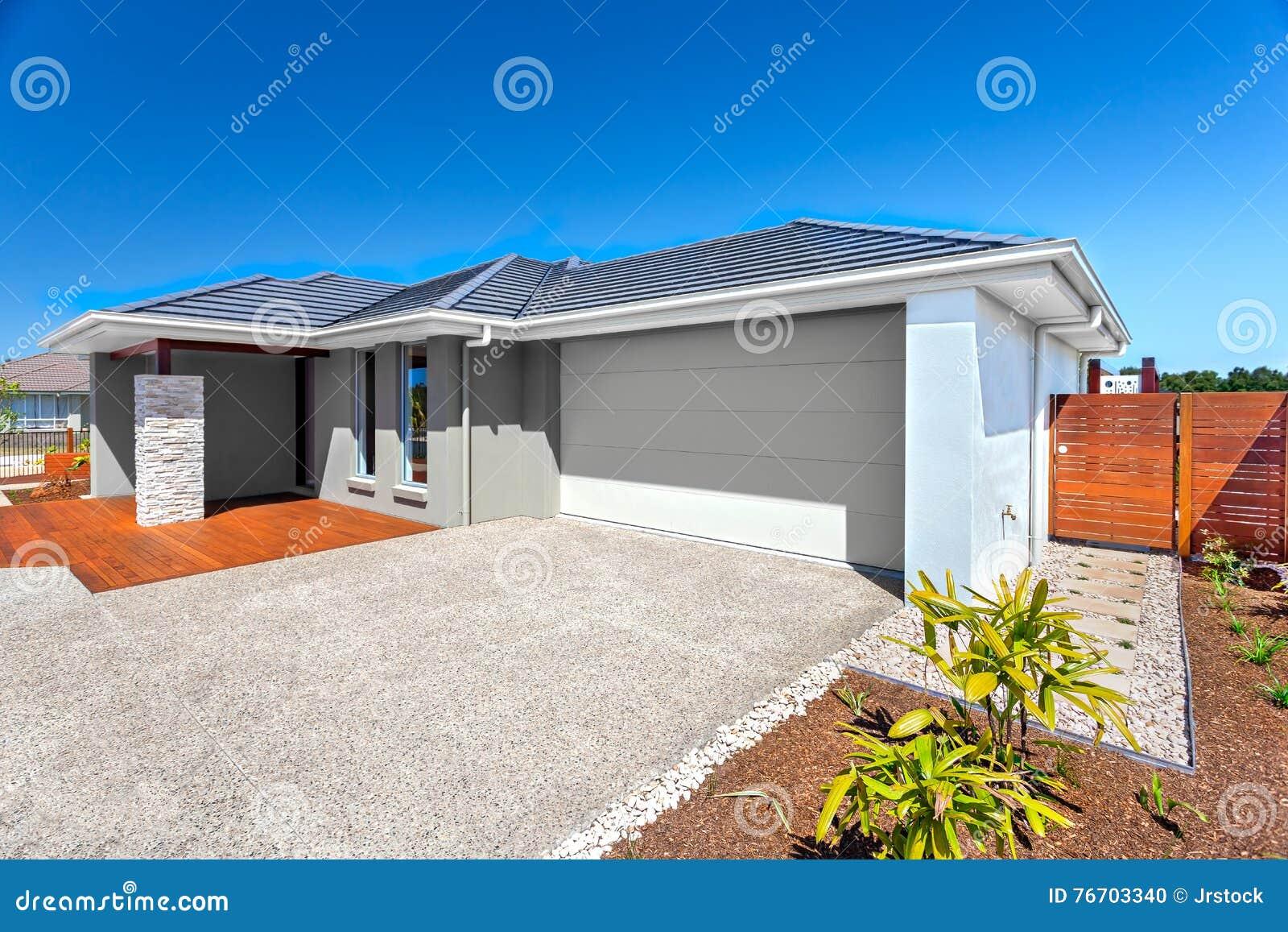 Modernt hus med ett garage- och trädgårdområde och blå himmel