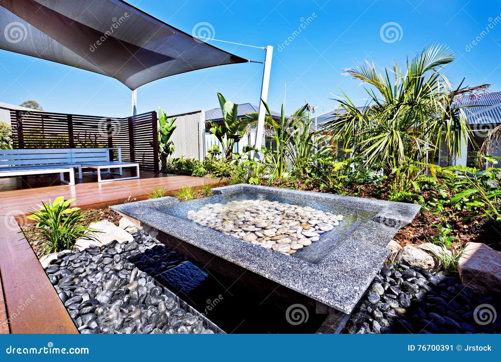 Modernt husuteplats och vattendamm med en trädgård