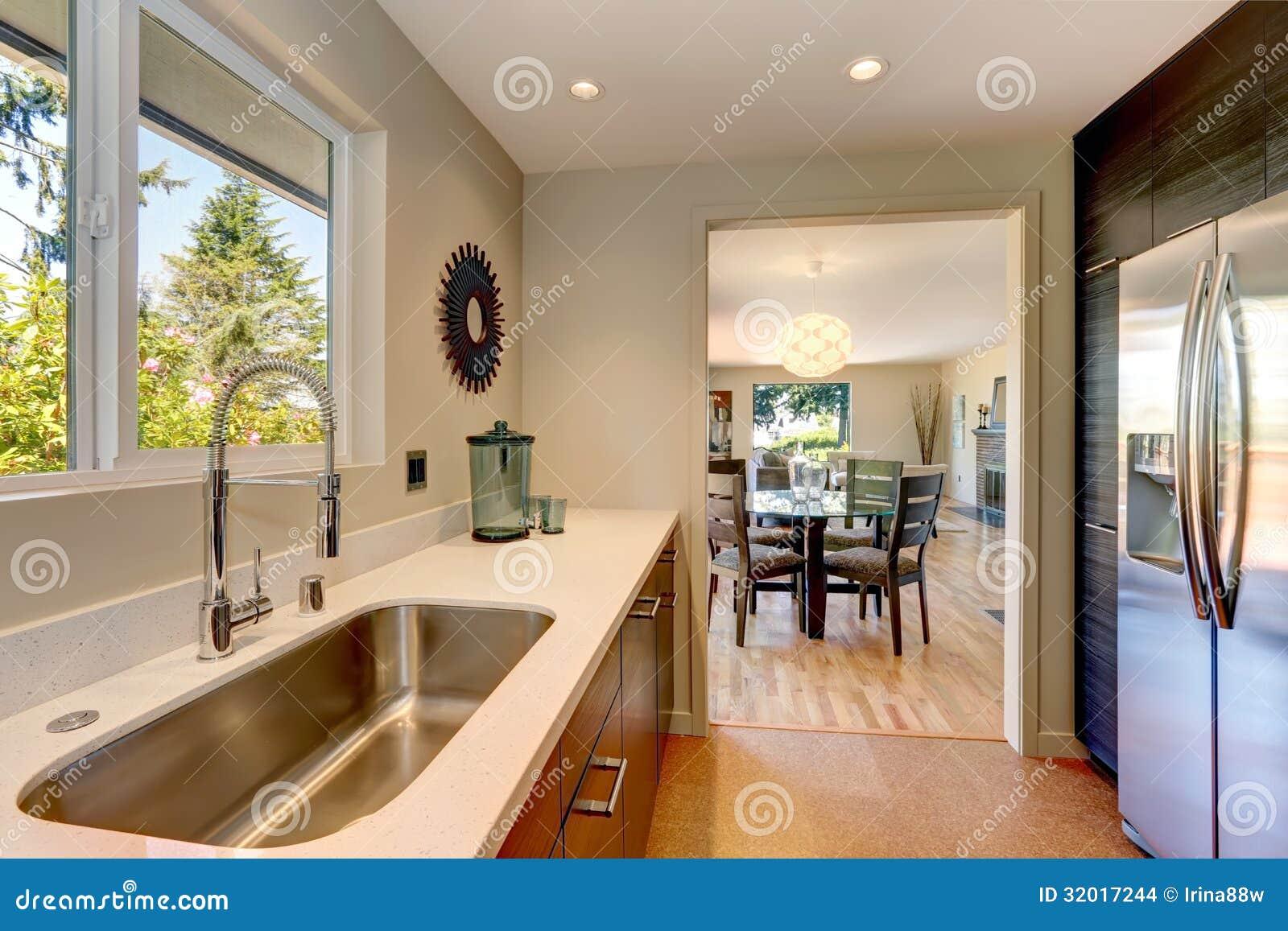 Modernt litet nytt kök med den stora vasken och vita countertops.
