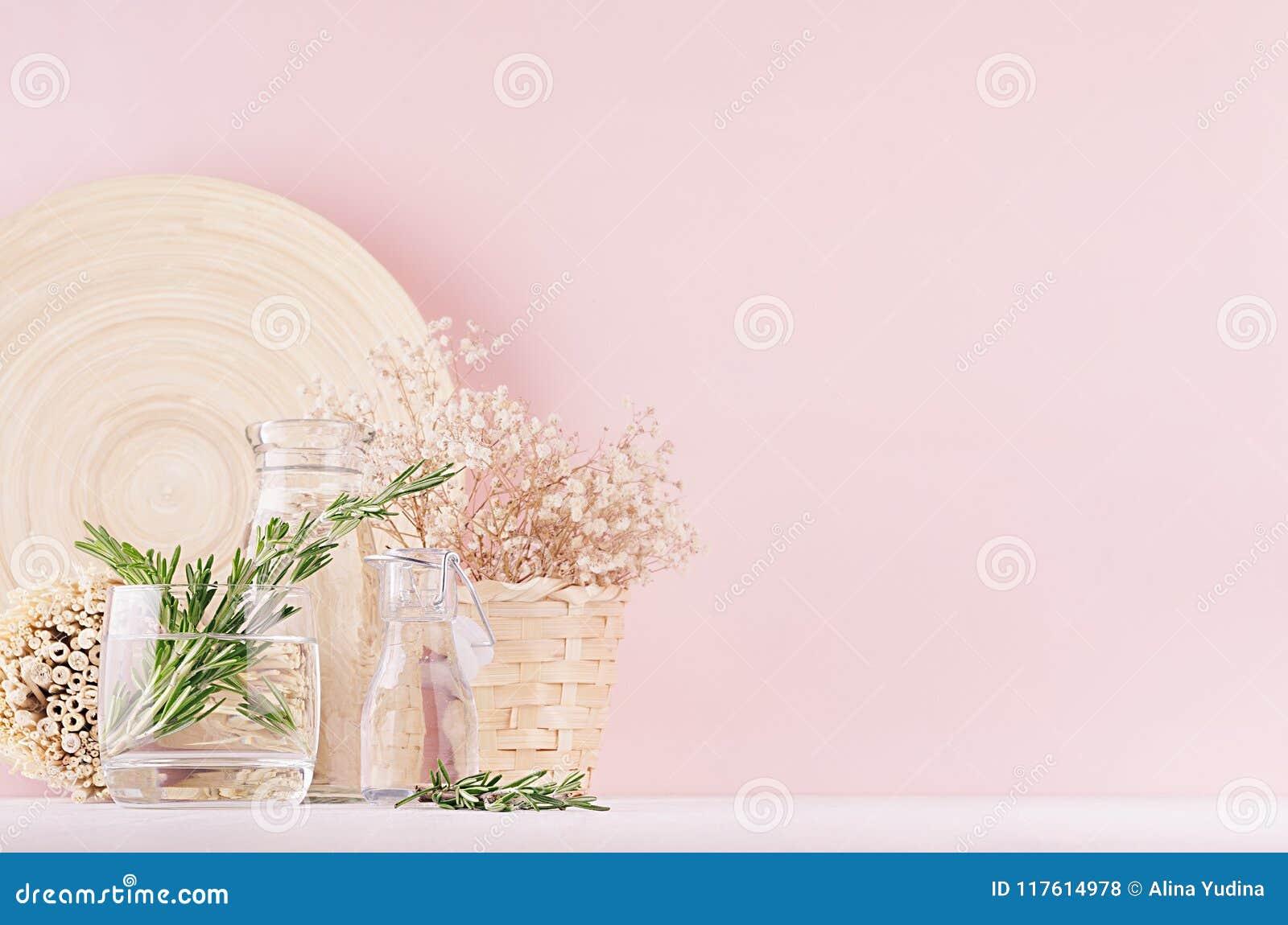 Modernt mjukt ljus - rosa pastellfärgad hemmiljö med den gröna växten, torkade vita blommor, beige bambuplatta på vit wood bakgru