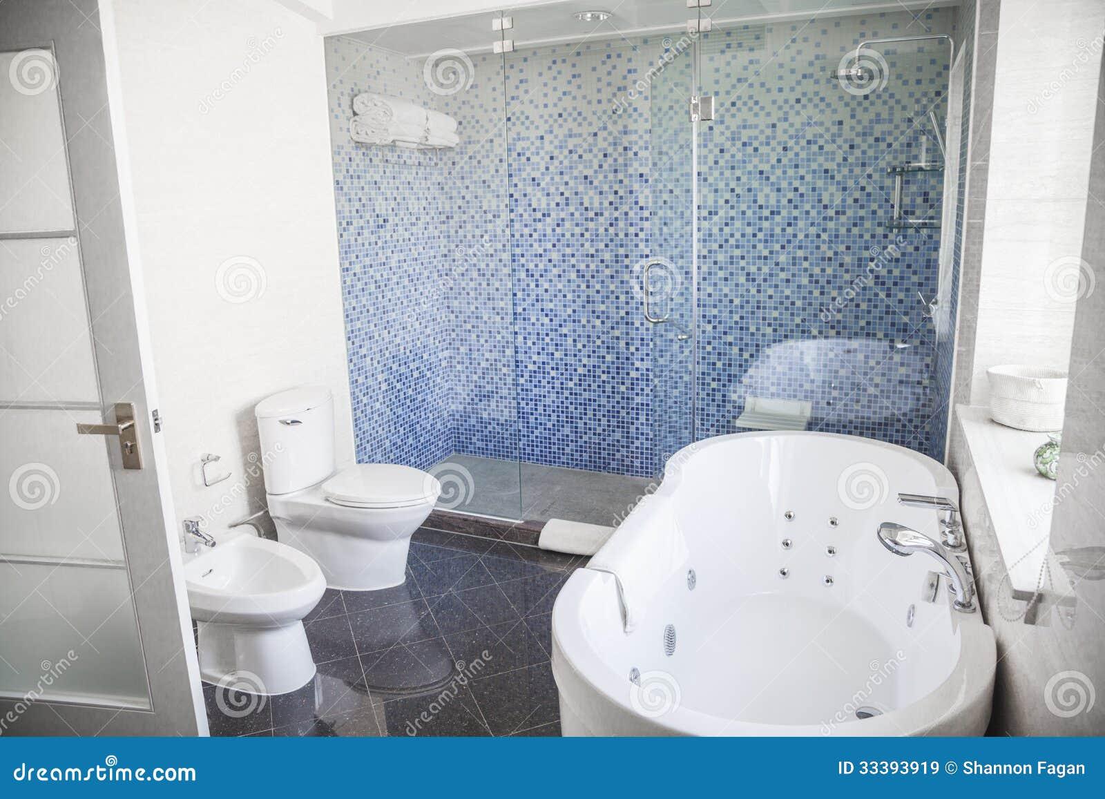 Modernt, rent, badrum med toaletten, vask, dusch och badkar ...