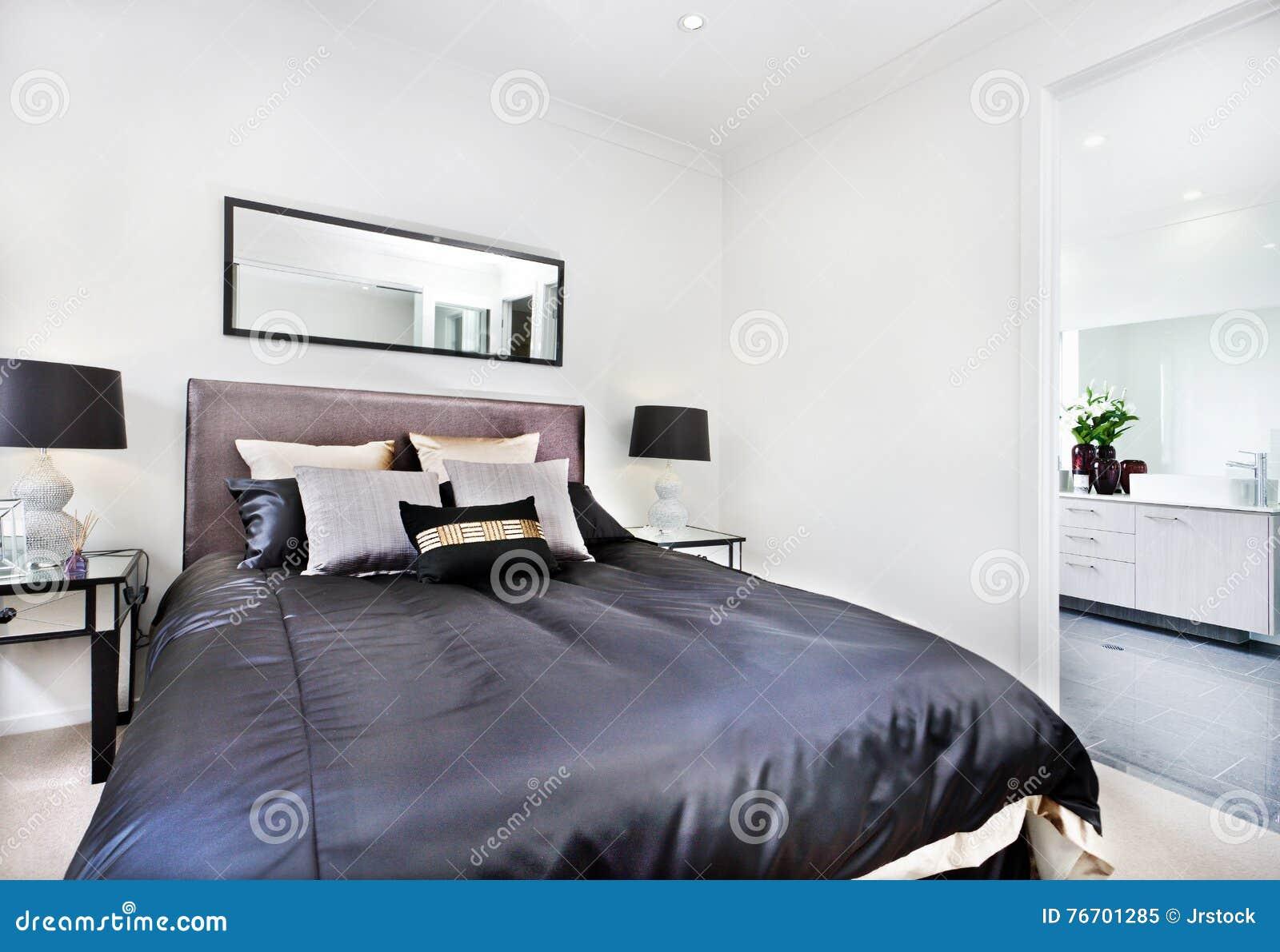 Modernt sängslut upp med den svarta madrassen bredvid badrummet