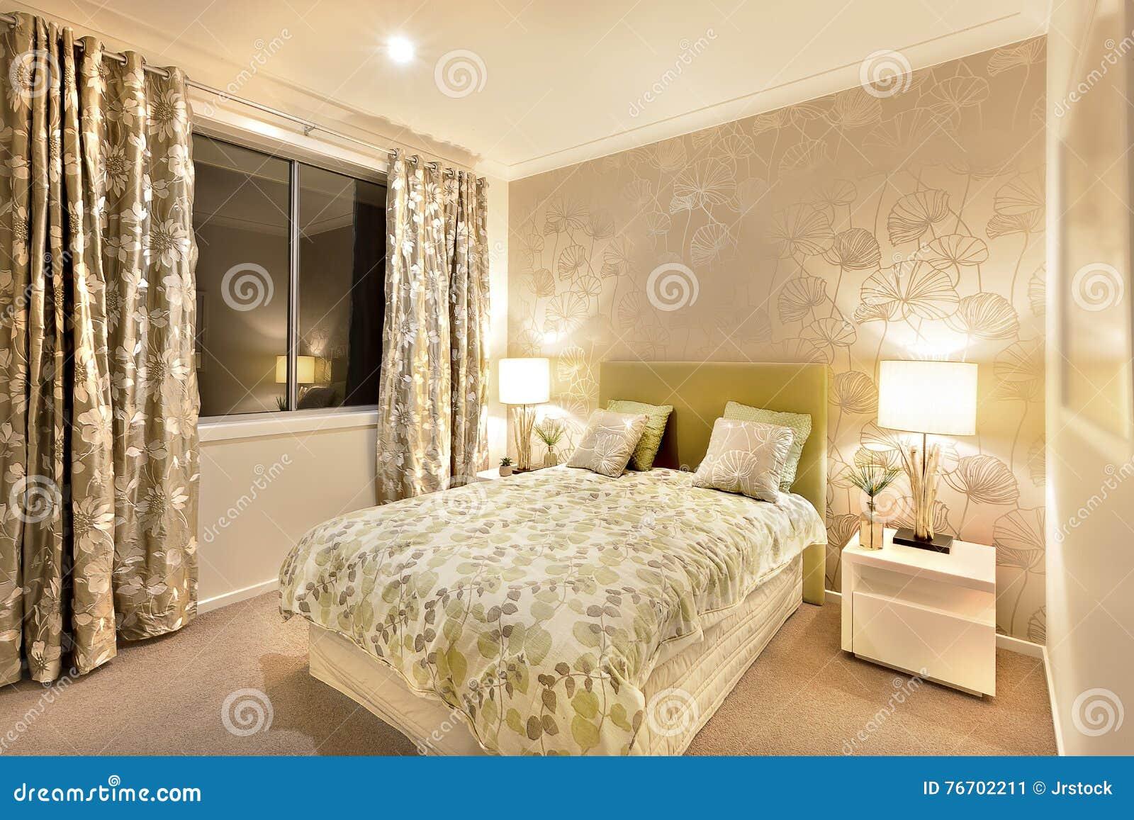Modernt sovrum med konungformatsäng som är upplyst vid tabelllampor