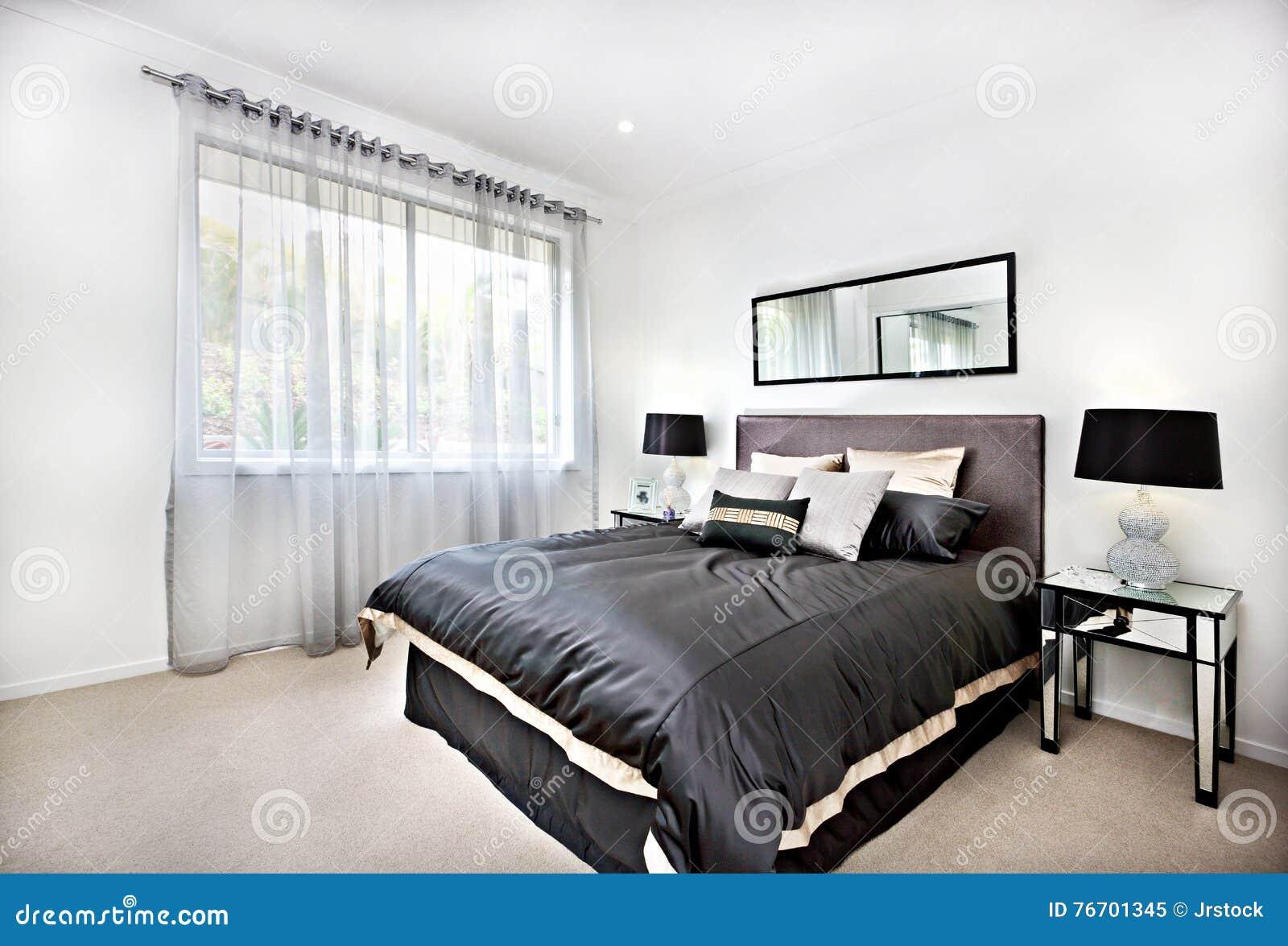 Modernt sovrum med svart garnering och spegel bredvid lampor