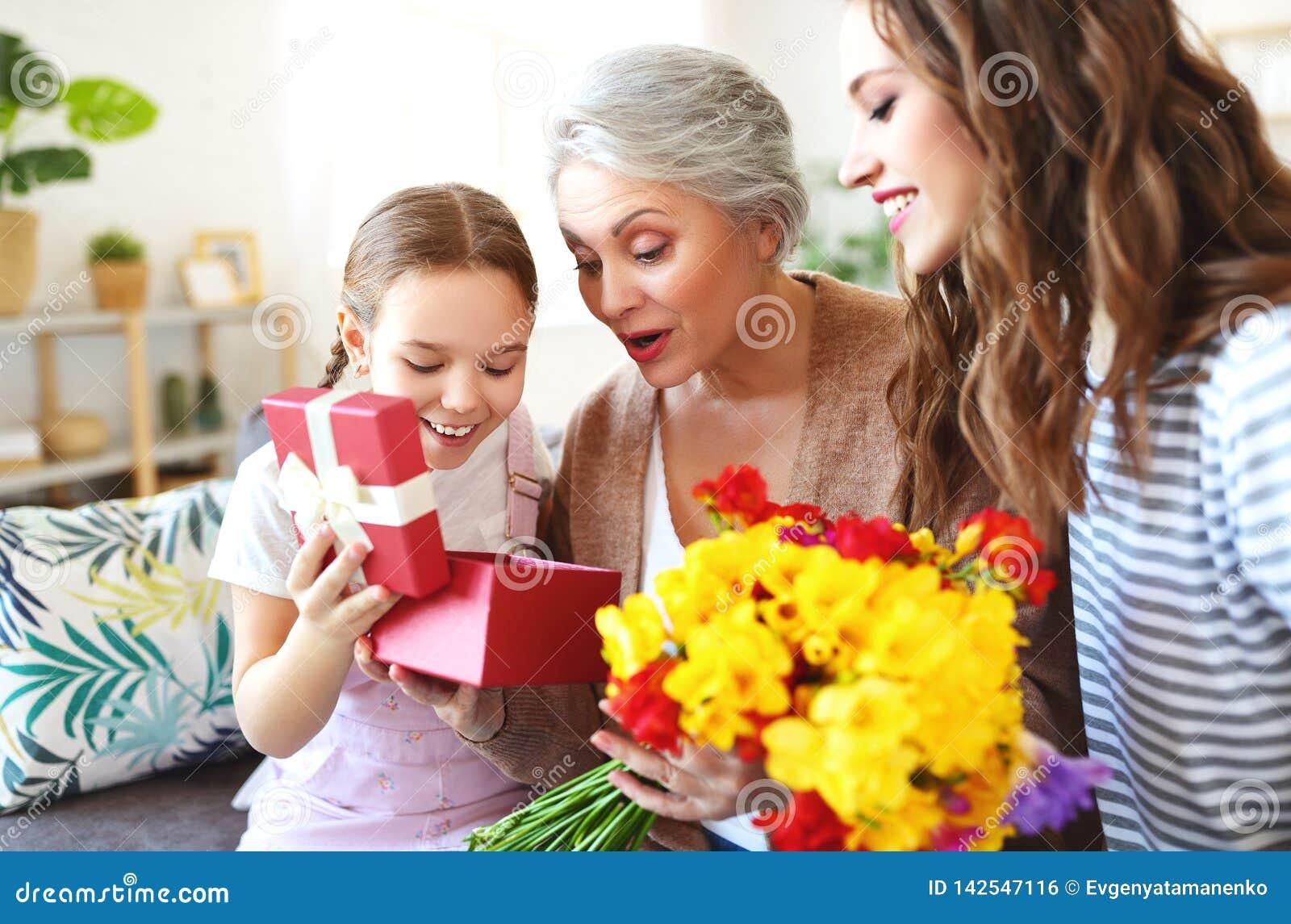 Moders dag! tre utvecklingar av familjmoder, farmor och dotter gratulerar på ferien, ger blommor