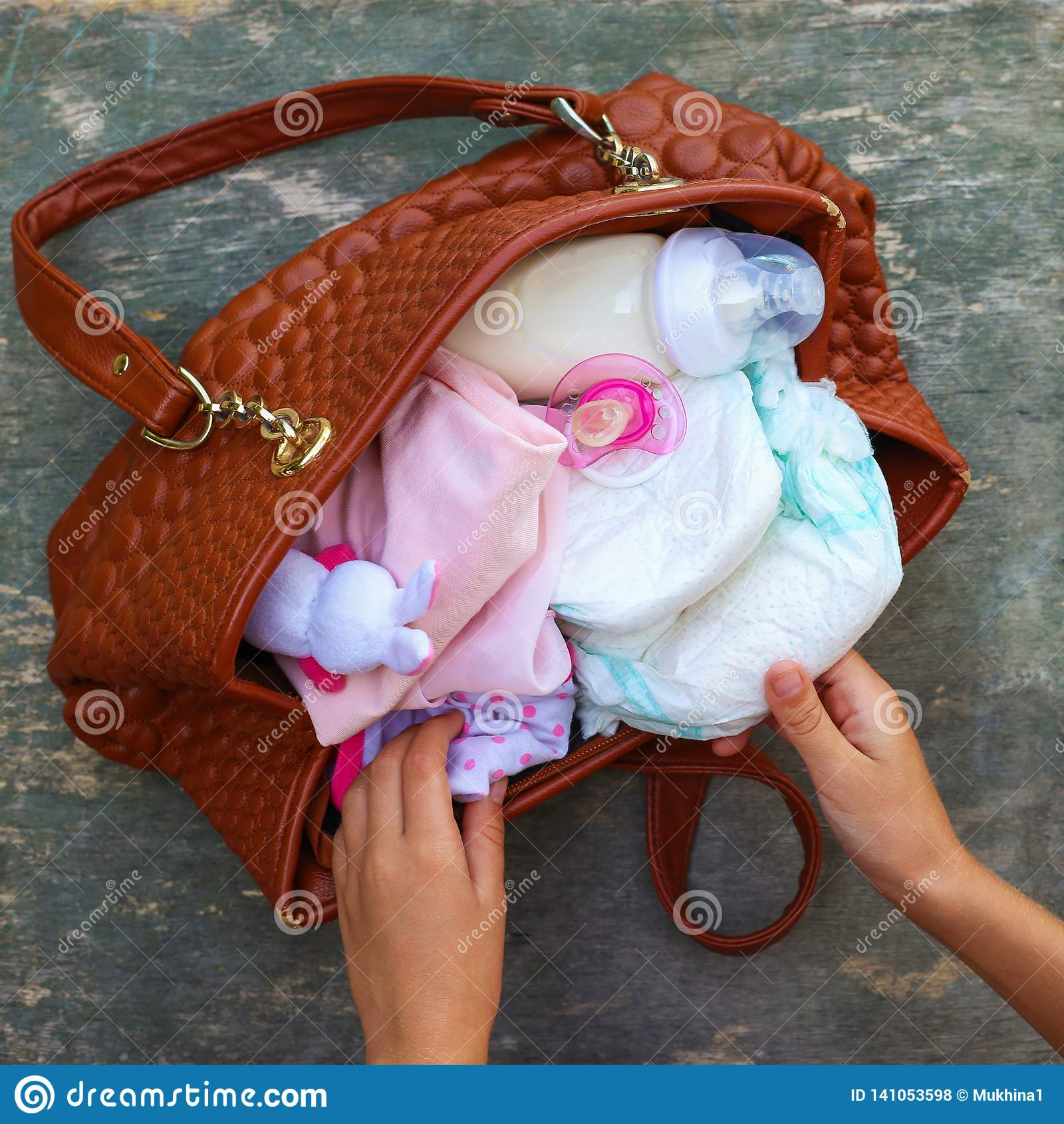Moders handväska med objekt som att bry sig för barn på gammal träbakgrund