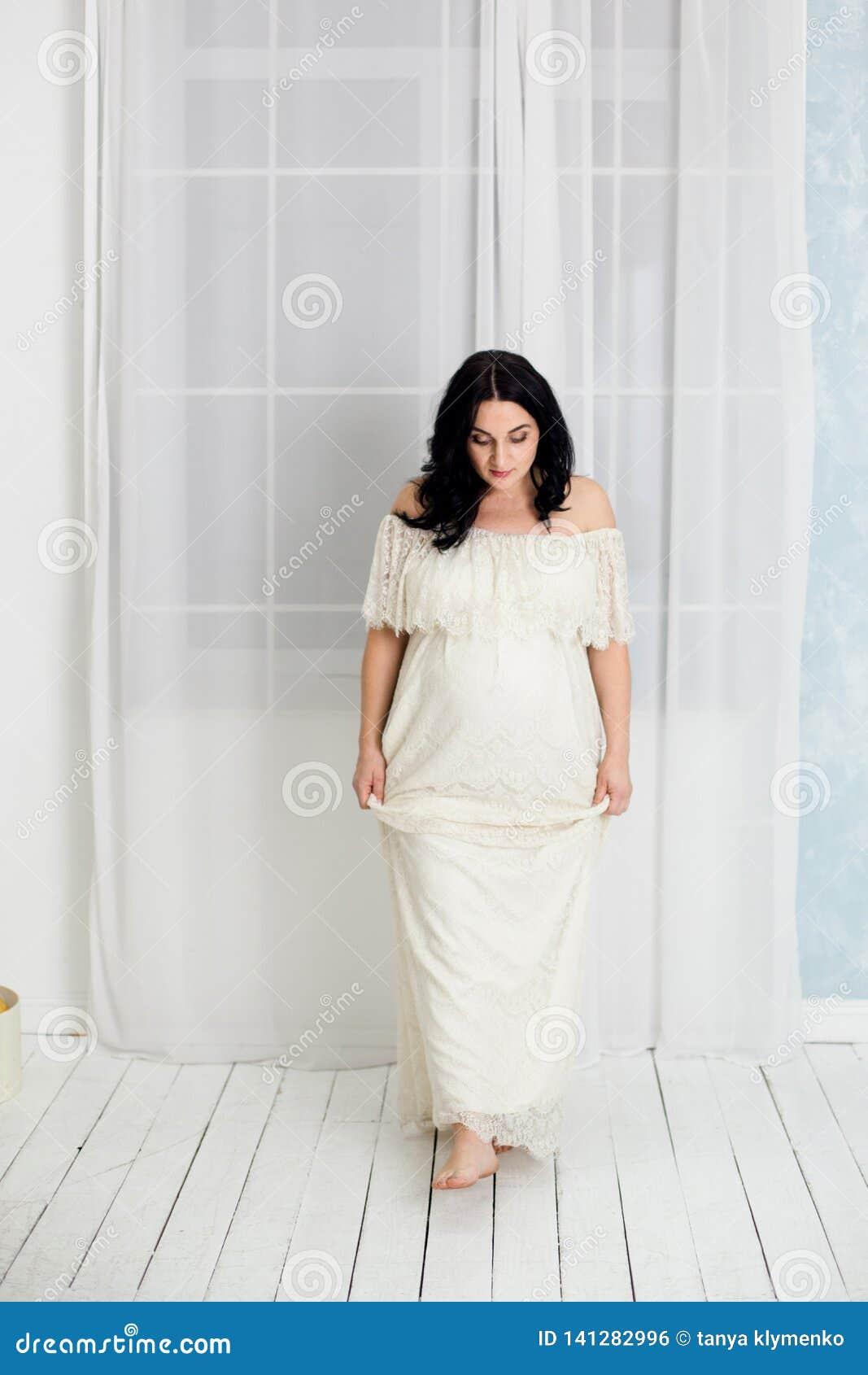 Modestående av den lyckliga gravida kvinnan i den vita klänningen