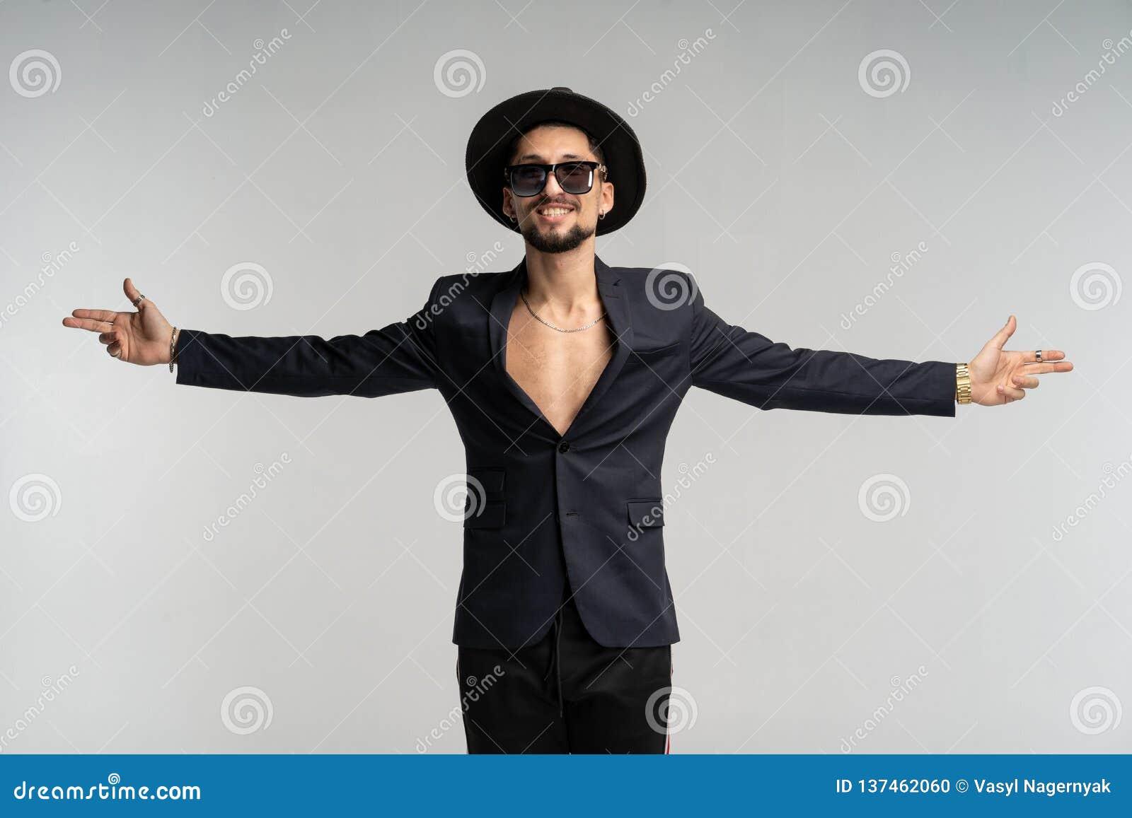 Modestående av den stiliga eleganta mannen i svart dräkt och hatten som poserar i studio