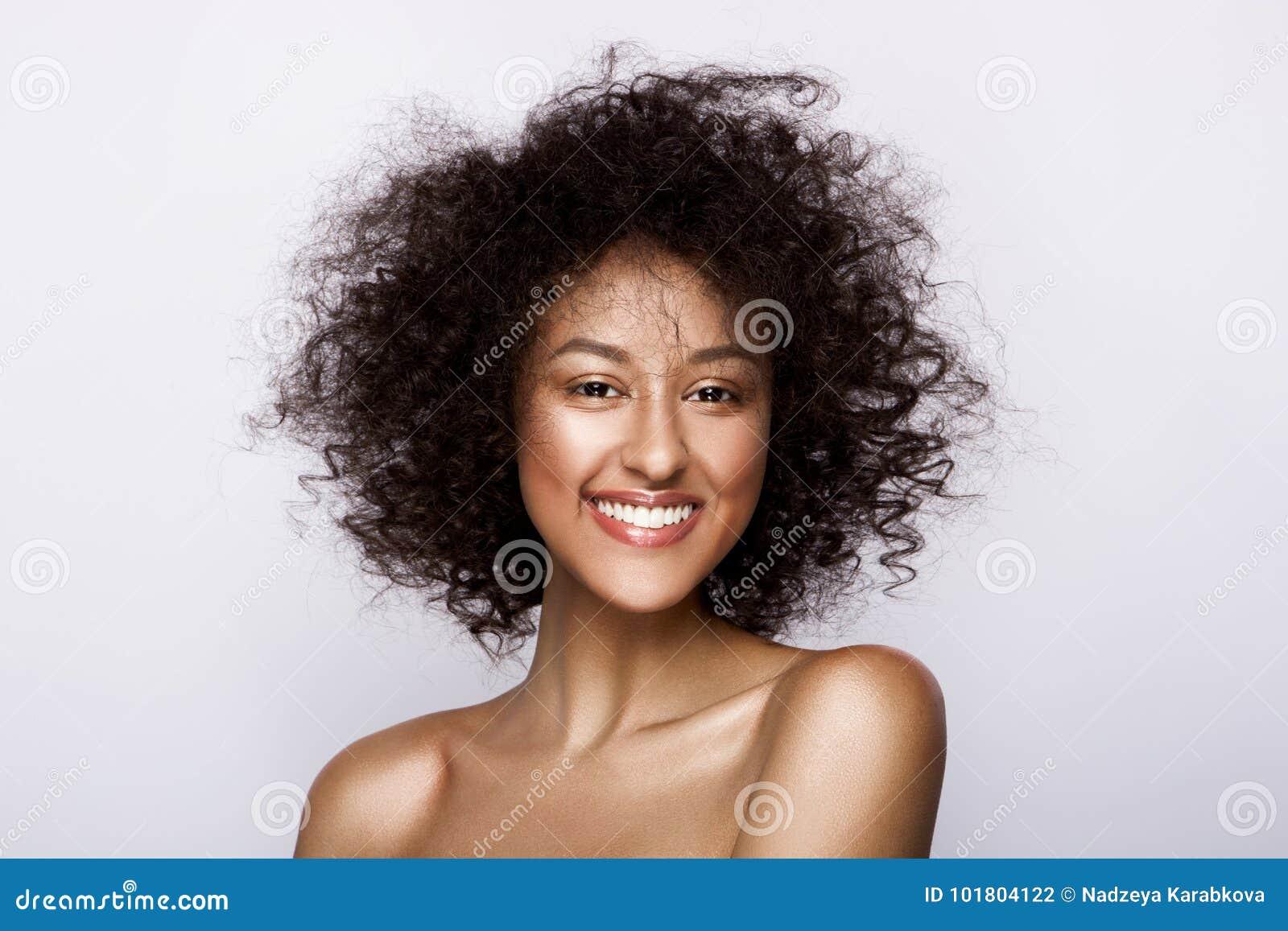 Modestudiostående av den härliga afrikansk amerikankvinnan med perfekt slät glödande mulatthud, smink