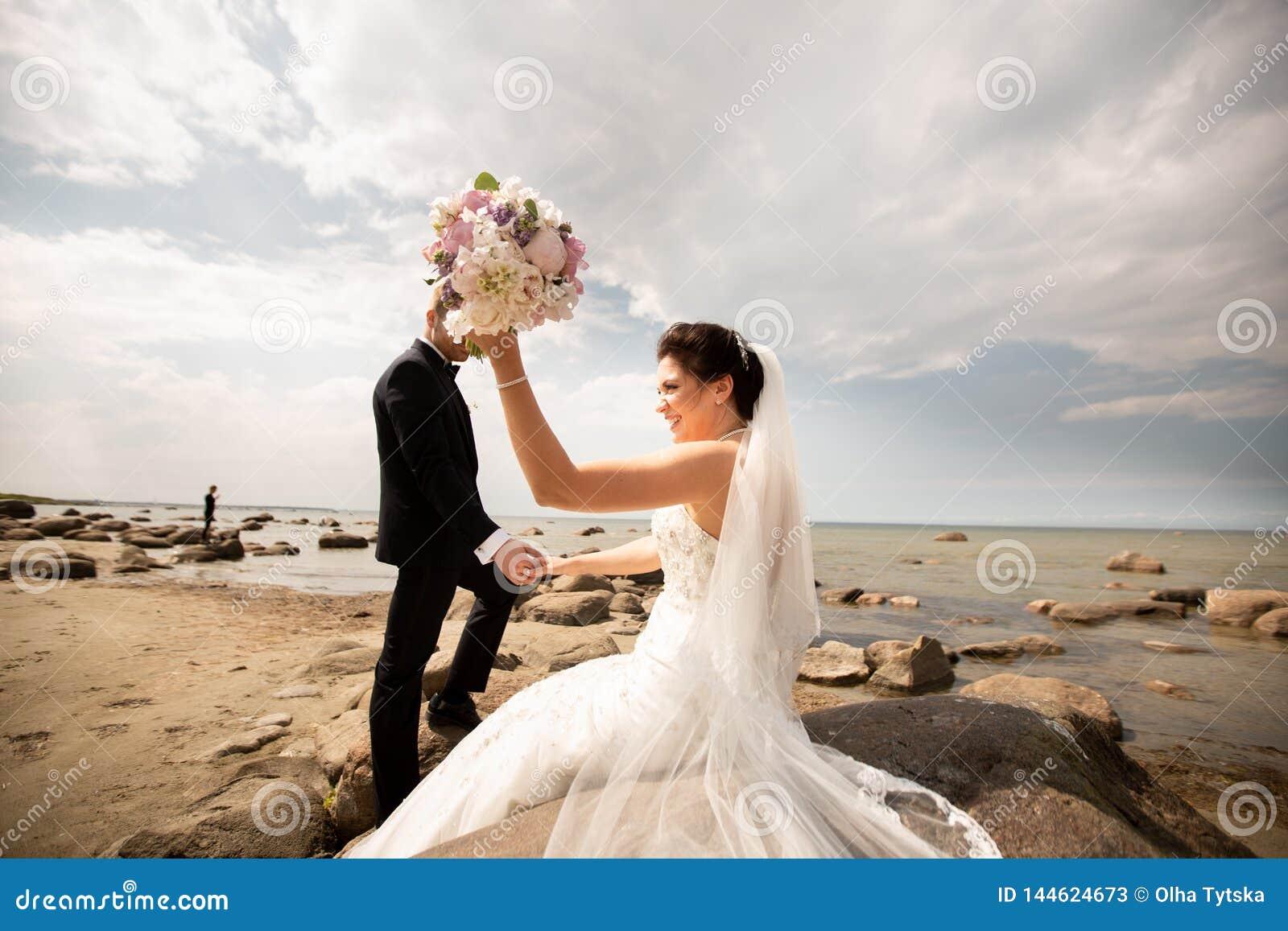 Modieus huwelijkspaar die zich op overzeese kust bevinden De jonggehuwden lopen door het overzees