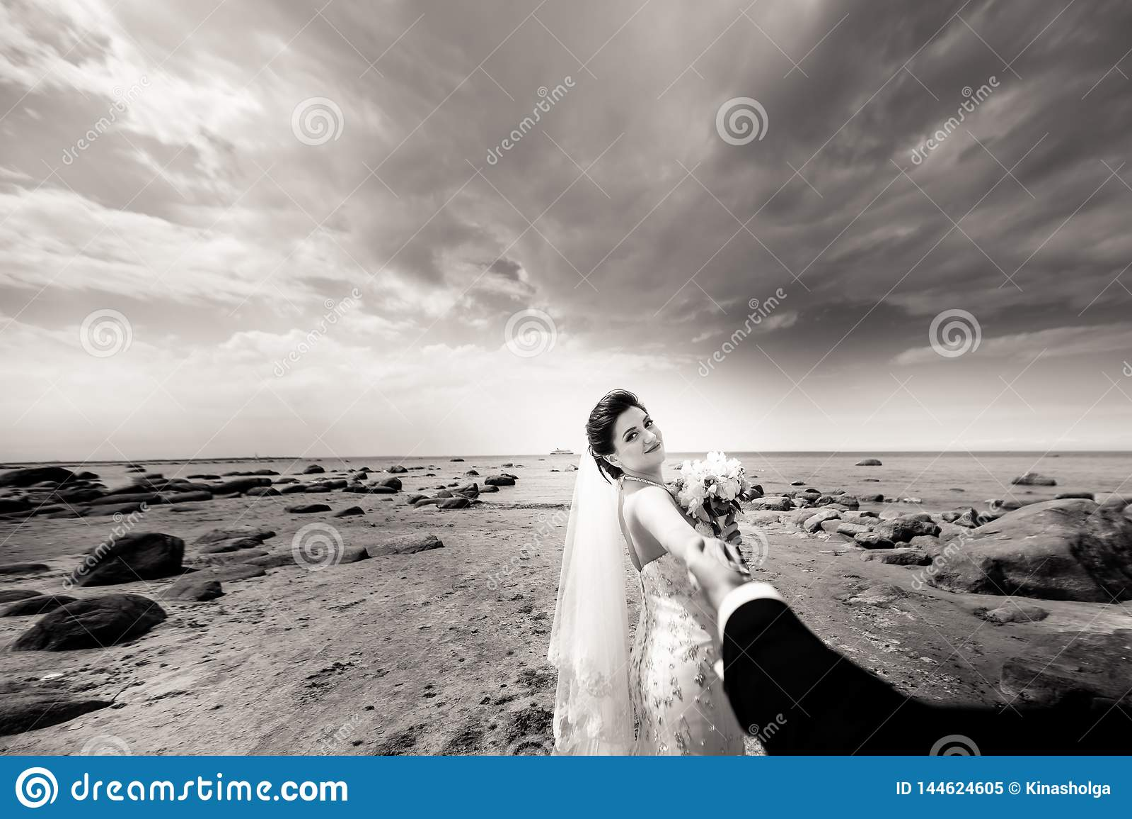 Modieus huwelijkspaar die zich op overzeese kust bevinden De jonggehuwden lopen door het overzees Rebecca 36