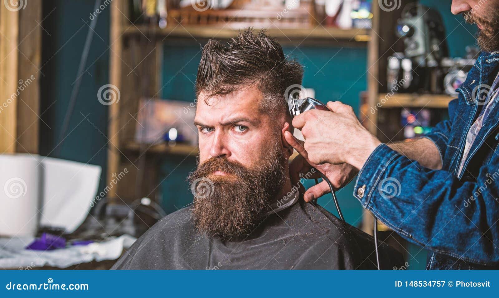 Modieus kapselconcept De handen van kapper met clipper sluiten omhoog Cli?nt met baard op salonachtergrond Gebaarde Hipster