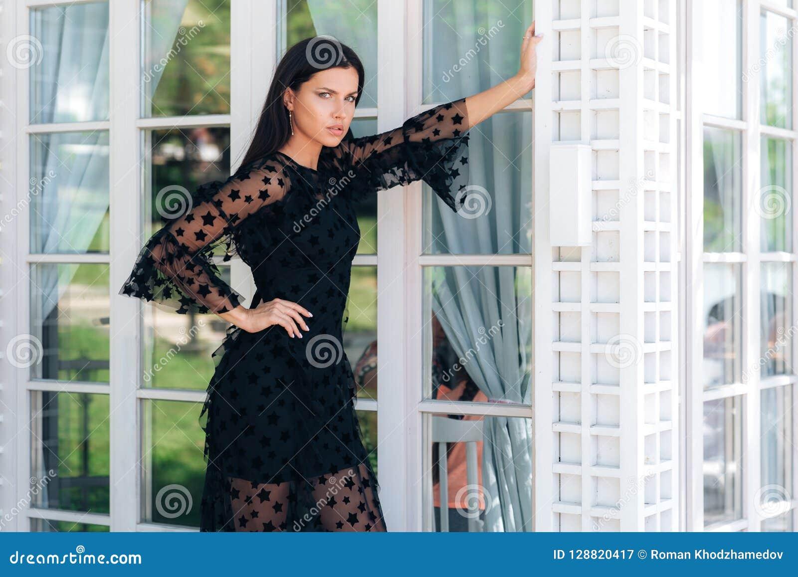 Modieus lang brunette met mooie lange benen die in een zwarte kledingsbuitenkant dichtbij een glasmuur stellen Een Aantrekkelijk