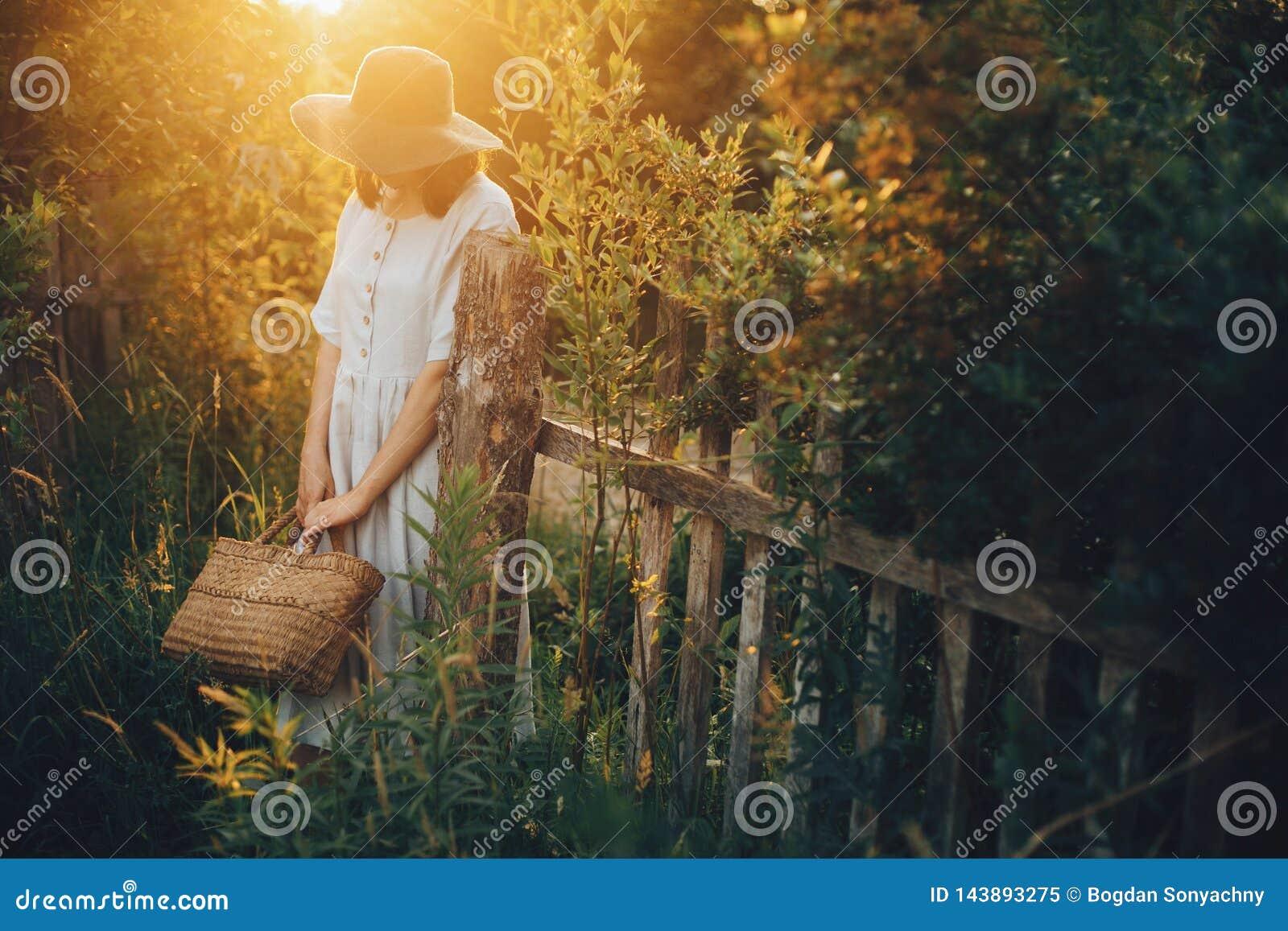 Modieus meisje in mand van het de holdings de rustieke stro van de linnenkleding bij houten omheining in zonsonderganglicht Bohov
